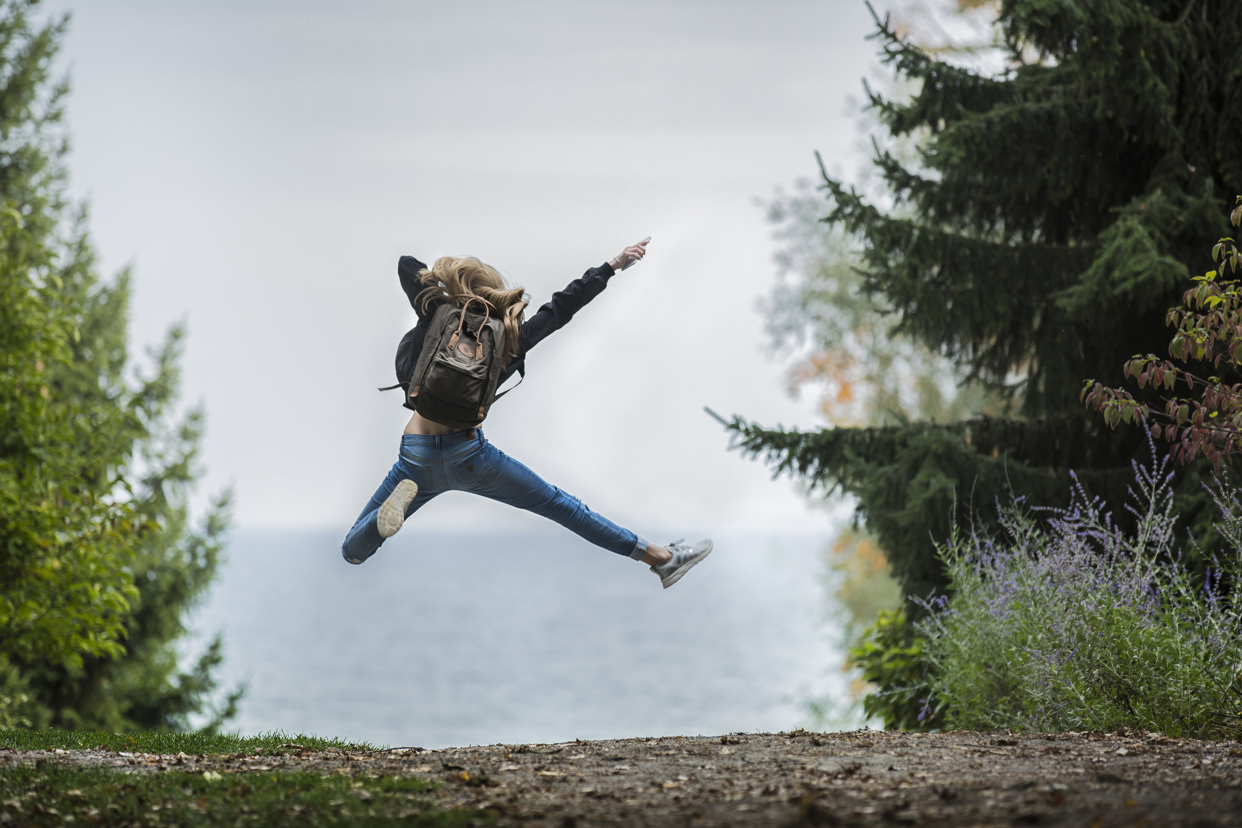 joyful teenager leaping in the air by Grand Traverse Bay, healthy teenager, adolescent counseling, therapy for teens