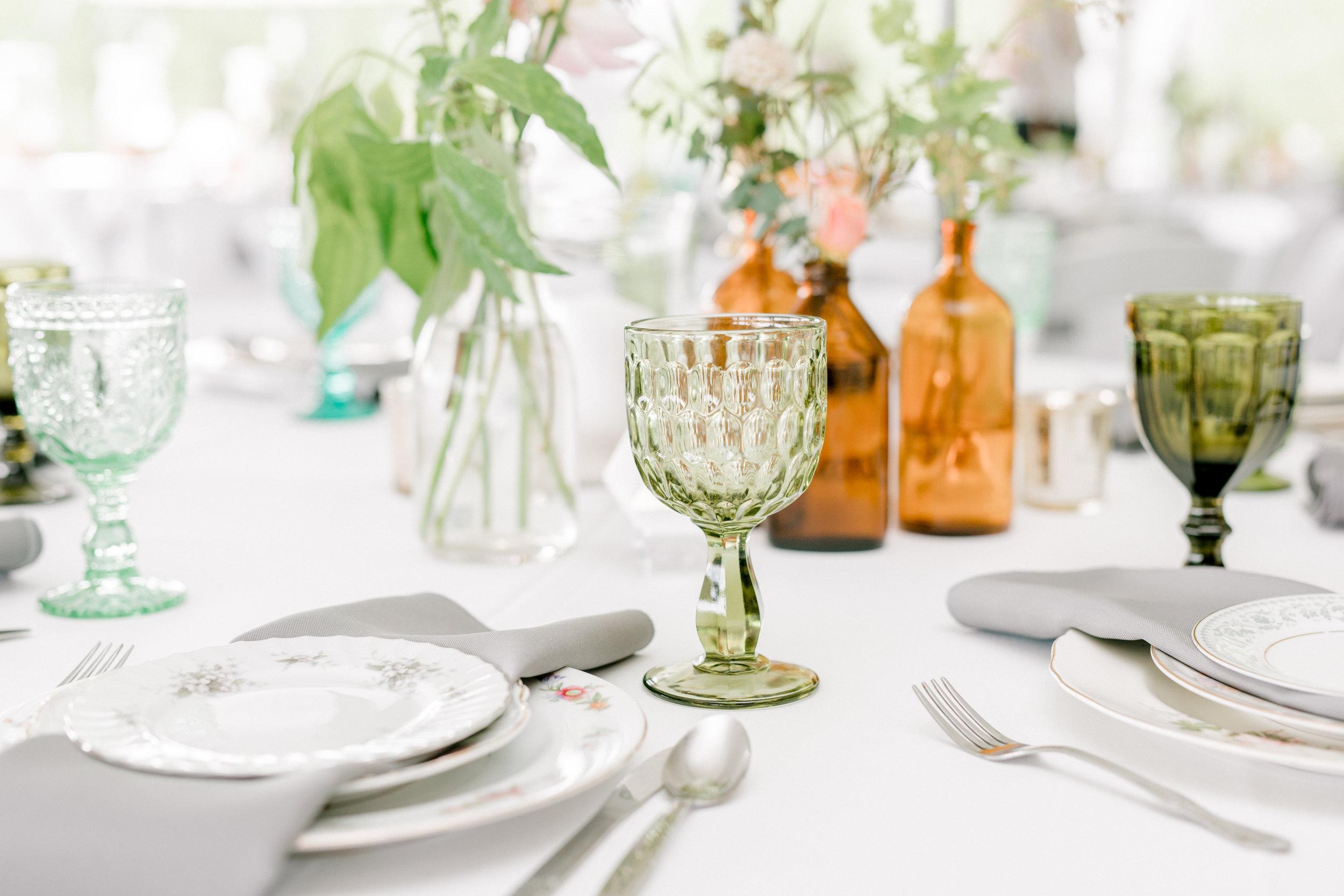 haley-richter-photography-summer-vineyard-winery-wedding-ecclectic-green-glass-goblet-glass-bottle-centerpiece-vintage-plates-gray-napkins