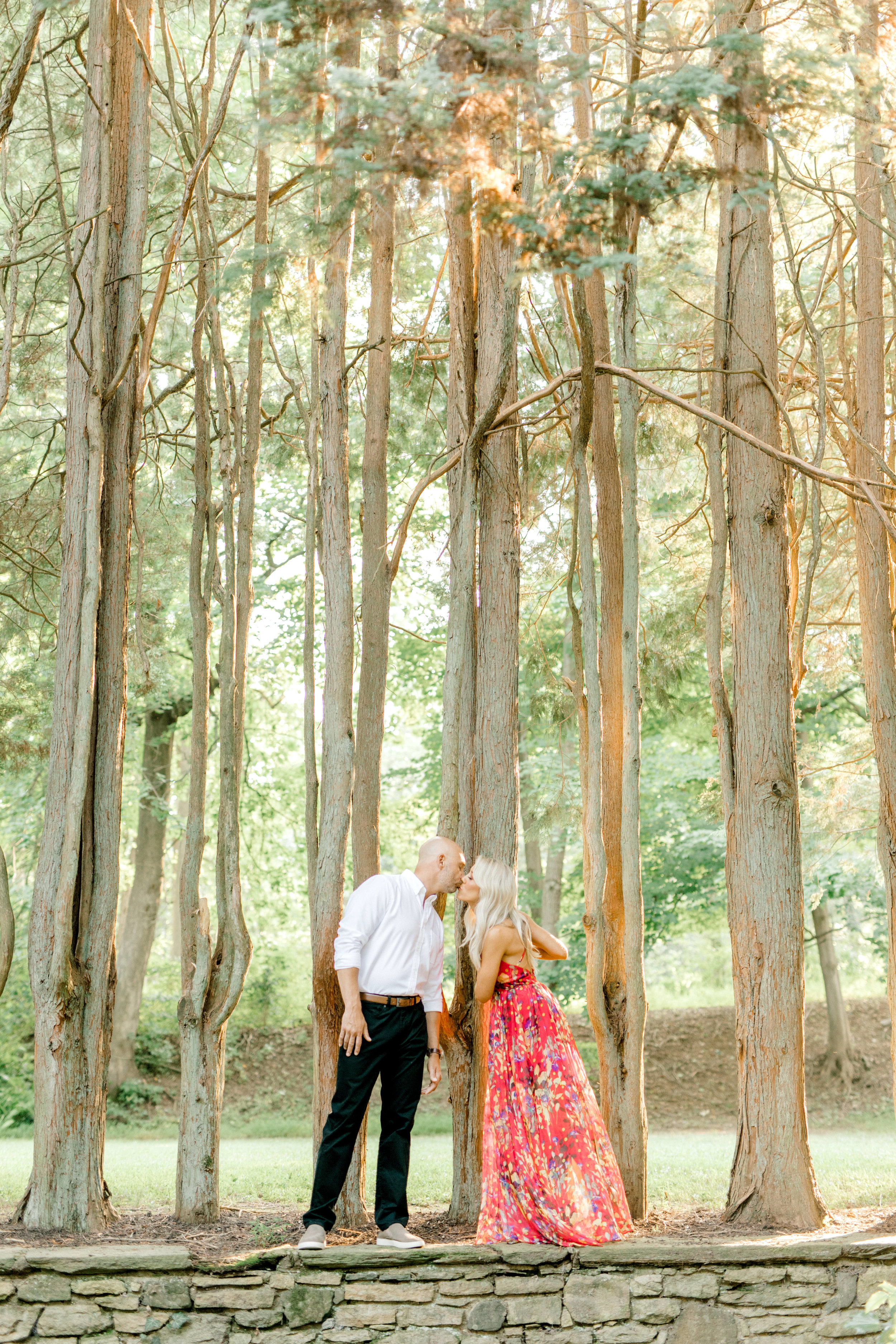 Liz and Bill share a kiss for their romantic sunset woodland engagement session at Parque at Ridley Creek