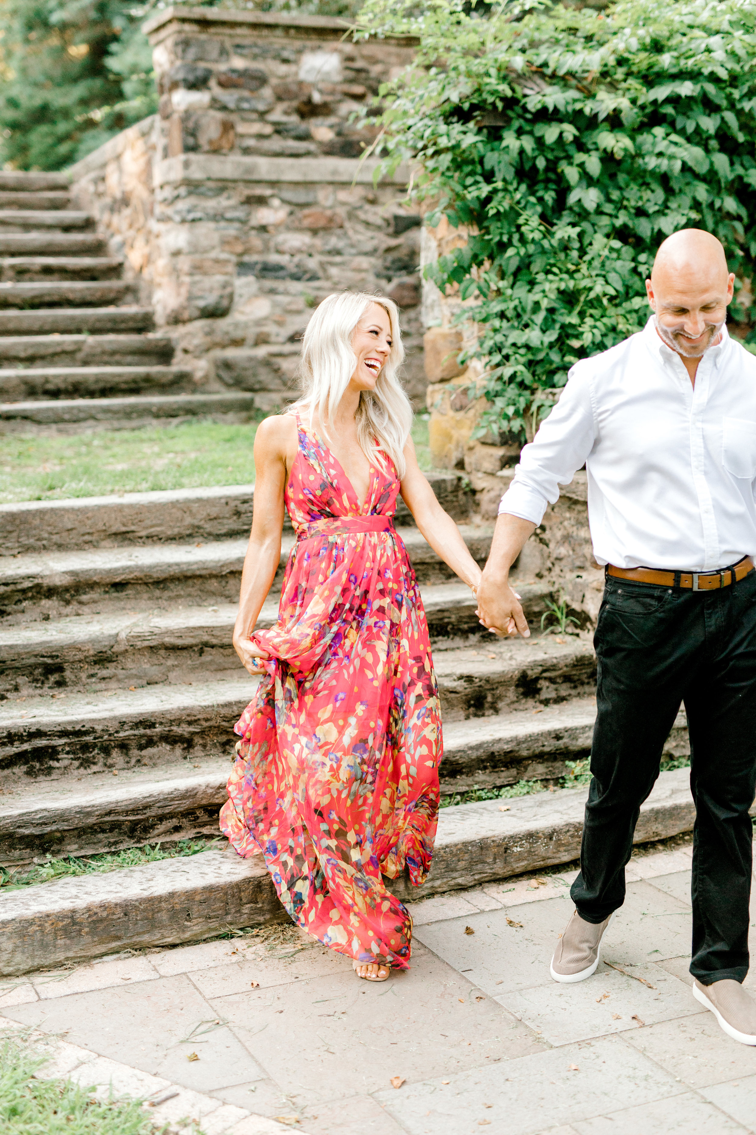 All smiles, these two know how to make each other laugh. And we simply adore this summery floral red dress that Liz chose for their romantic sunset woodland engagement session at Parque at Ridley Creek