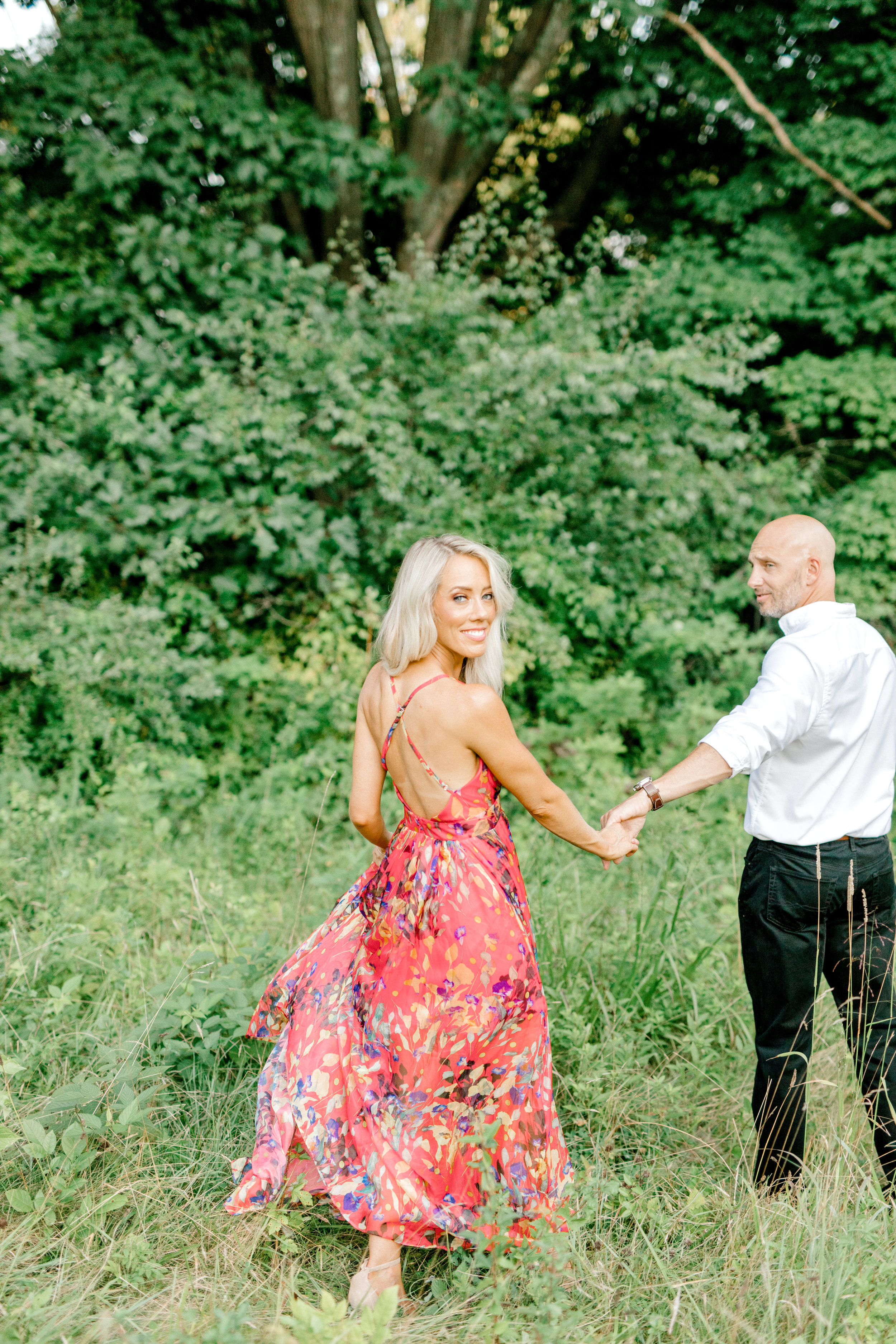 Liz looks back as her man holds her hand, leading her into their forever during their romantic sunset woodland engagement session at Parque at Ridley Creek