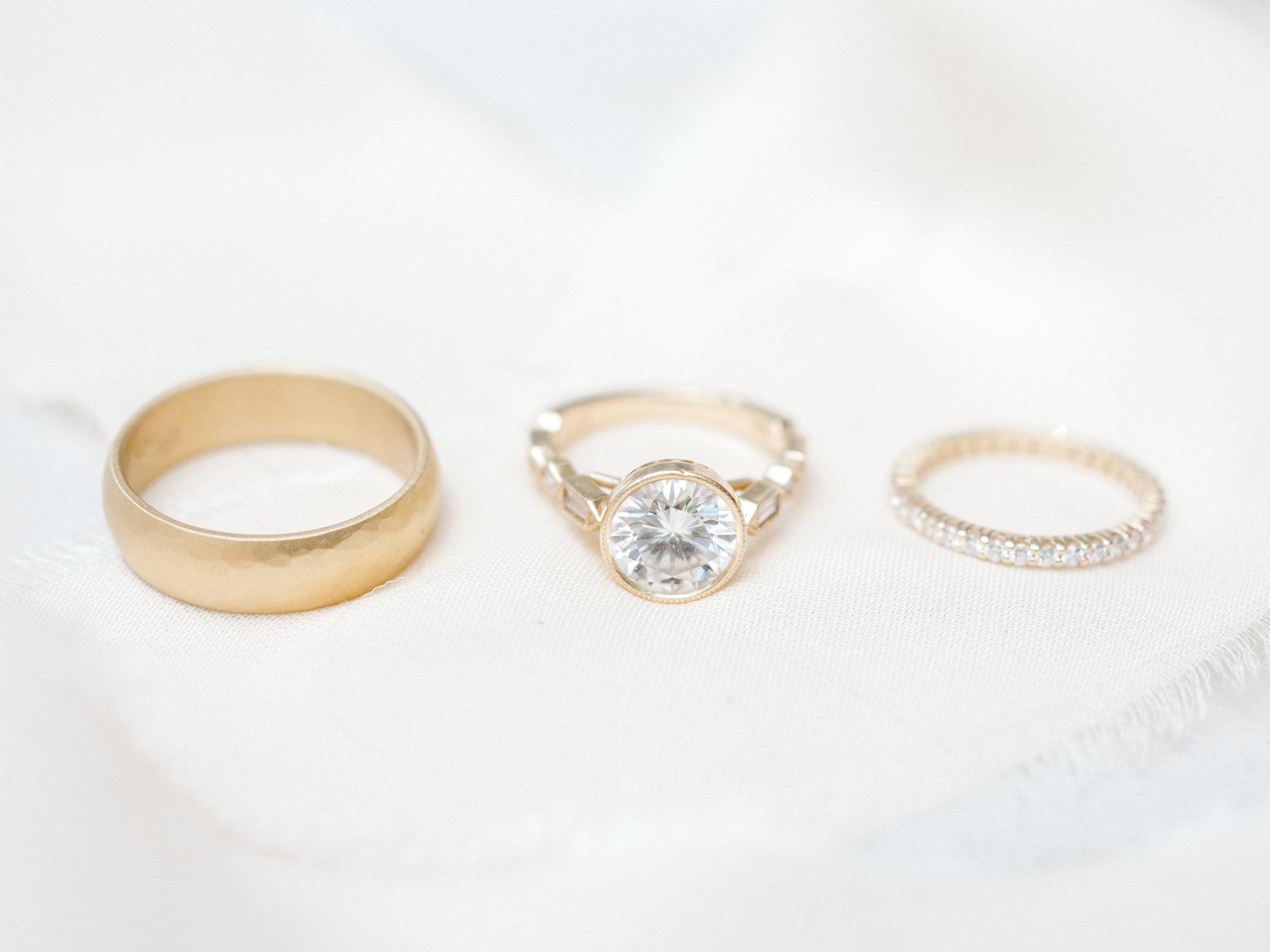 Modern gold wedding rings. Large white circular diamond engagement ring with modern gold fitting.