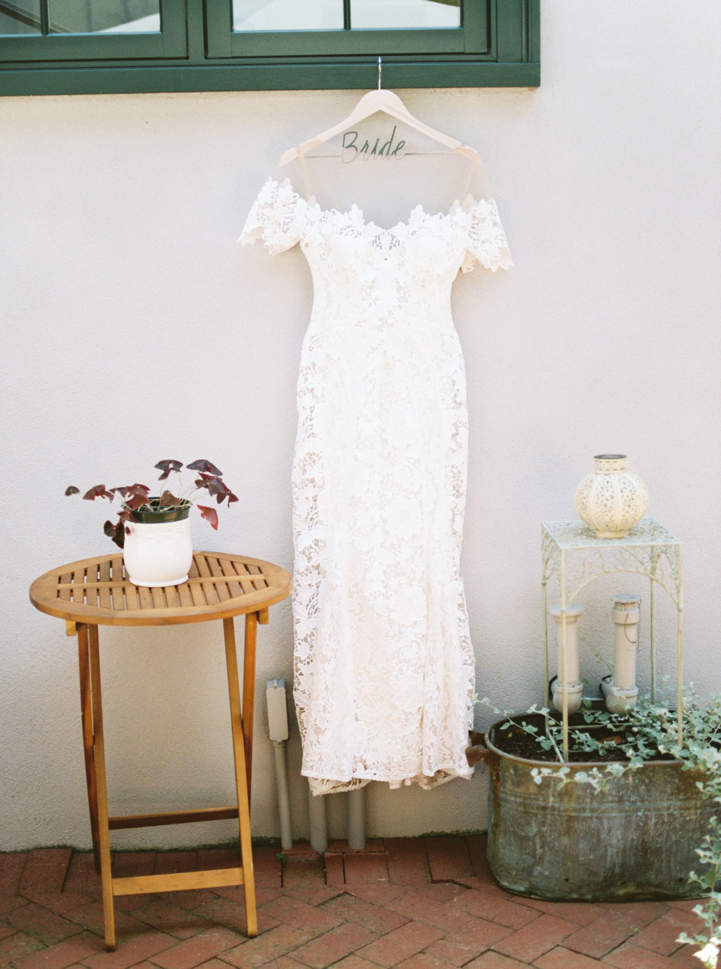 Classy white lace cap-sleeved wedding dress from Lover's Society for a modern summer wedding at Hotel du Village.