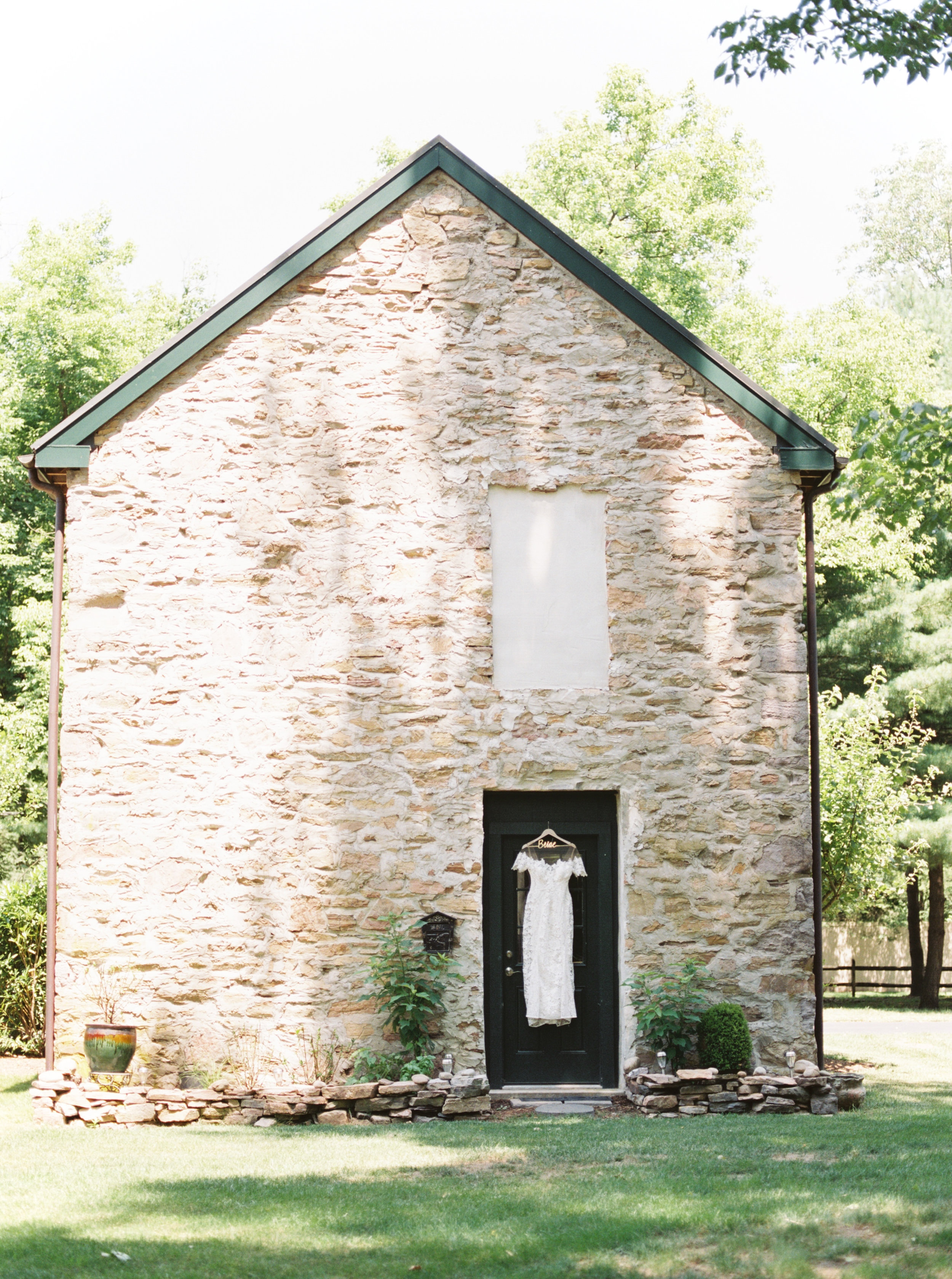 Pastoral vibes from this modern lace Lover's Society wedding dress hanging on this old stone building. A summer dream.