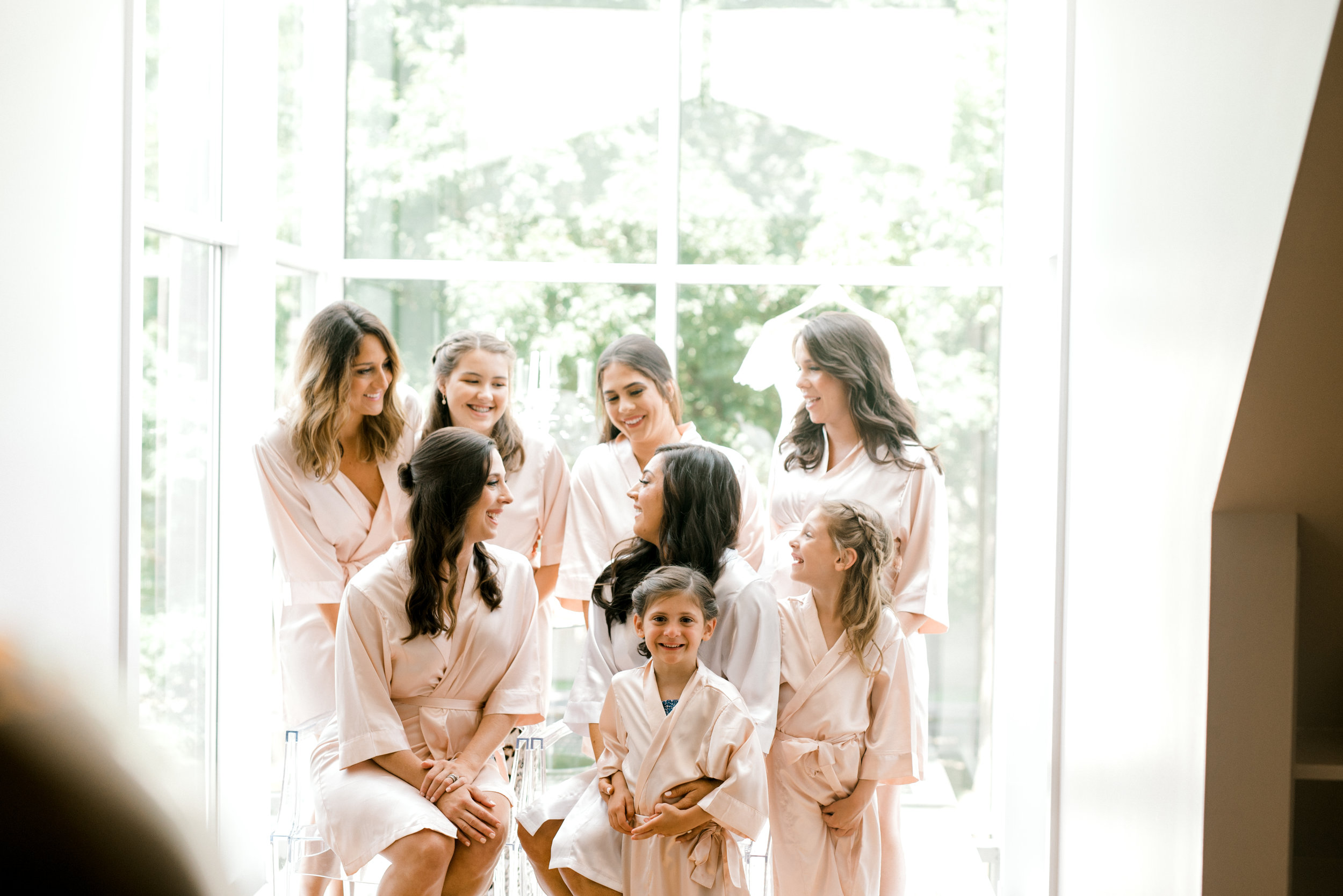 All the girls getting ready in their pink robes before a colorful and modern wedding day at Hotel du Village.
