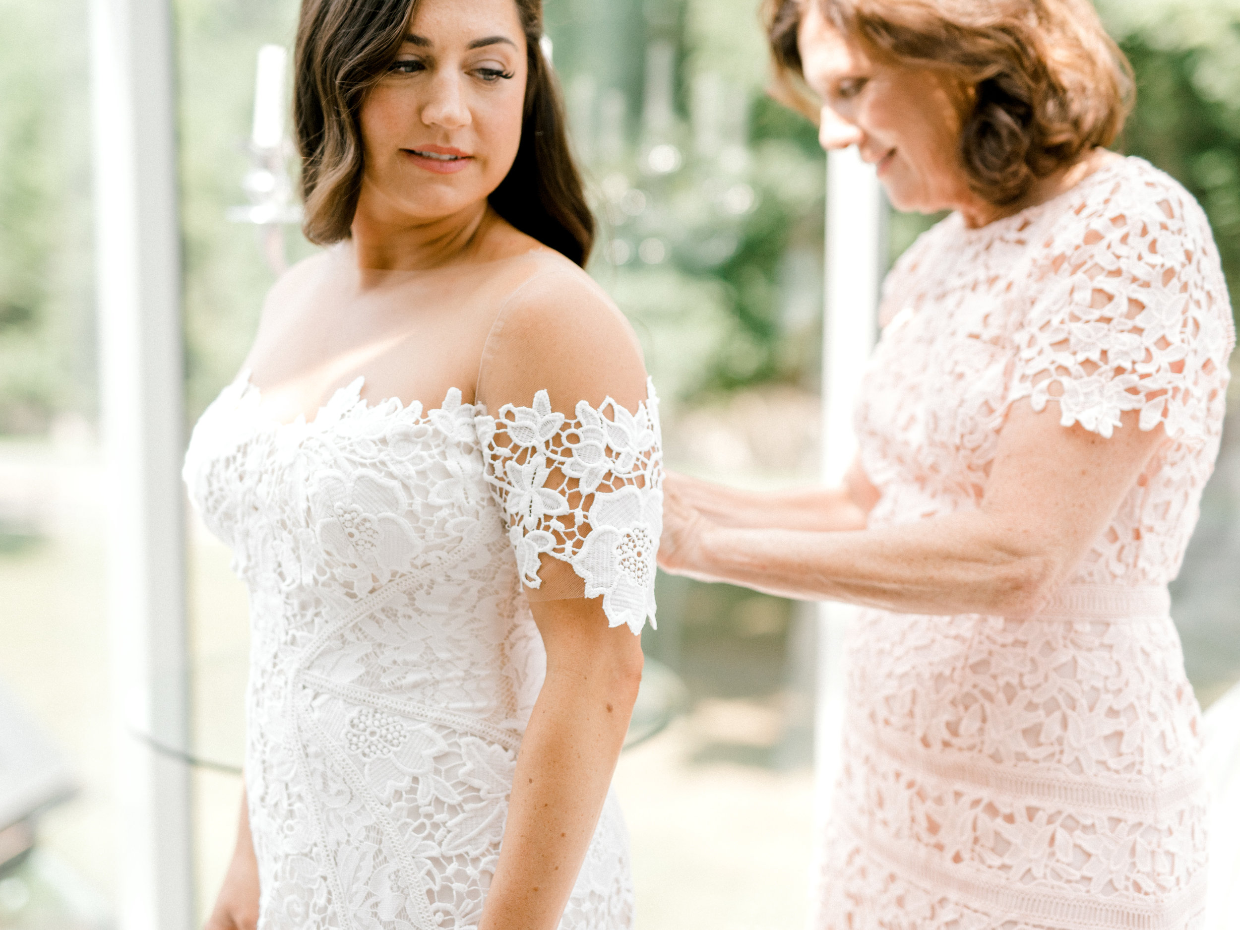 Lindsey's mom helps her get into her Lover's Society dress in this light filled AirBnb before her colorful and modern wedding day at Hotel du Village.