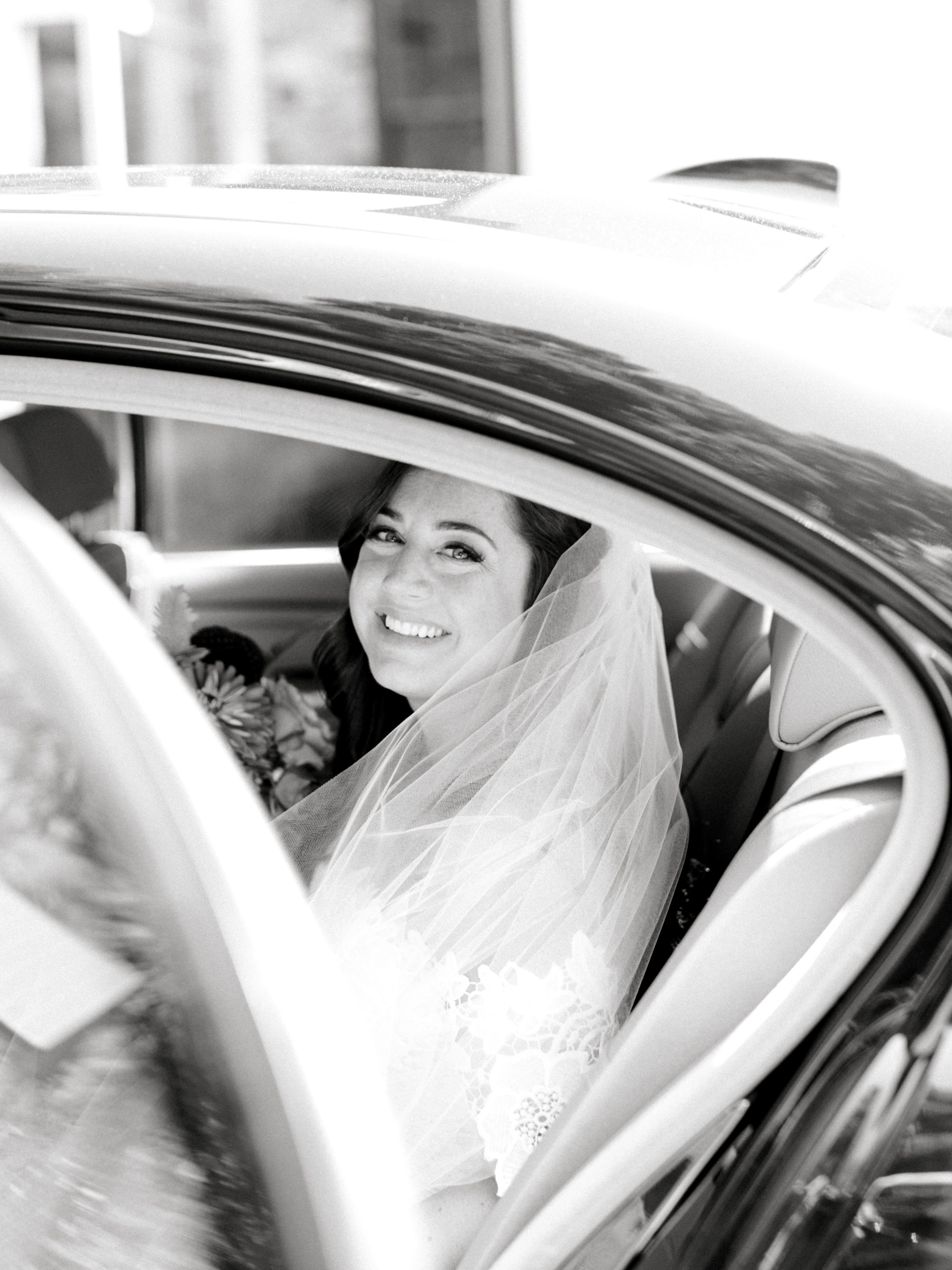 Lindsey is all smiles as she gets in the car ready to head off to her modern summer wedding at Hotel du Village.