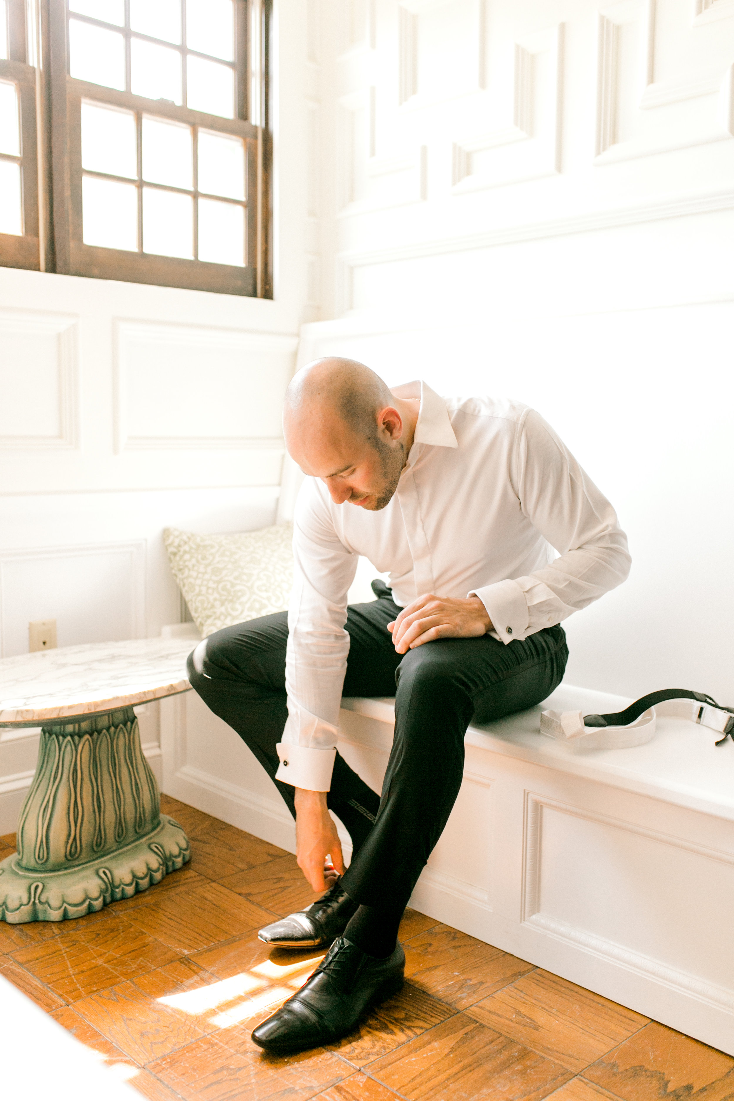 James gets ready in the bright sun-filled bridal suite of Hotel du Village for his modern summer wedding.