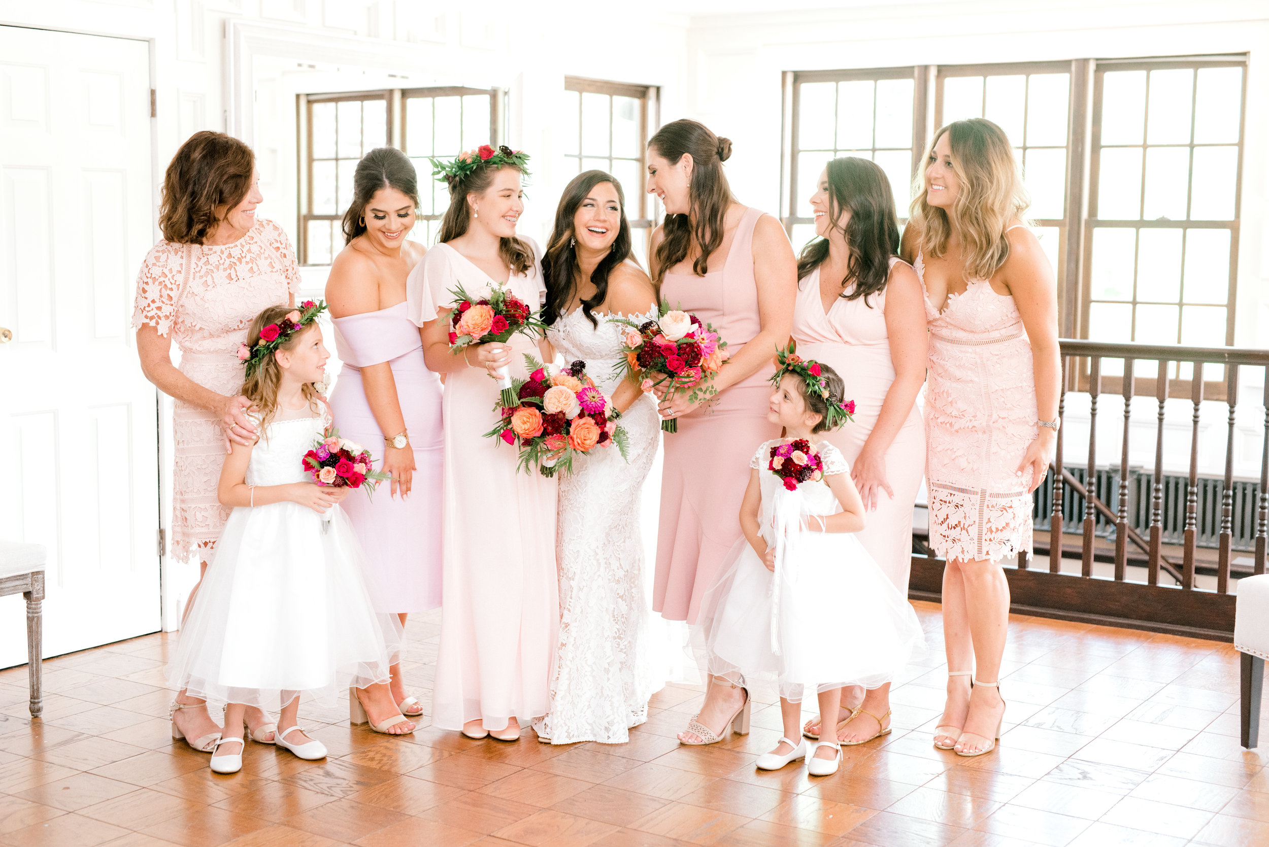 We loved the mix of pale pinks and whites with a pop of bright florals for this bridal party for a modern and colorful summer wedding at Hotel du Village.