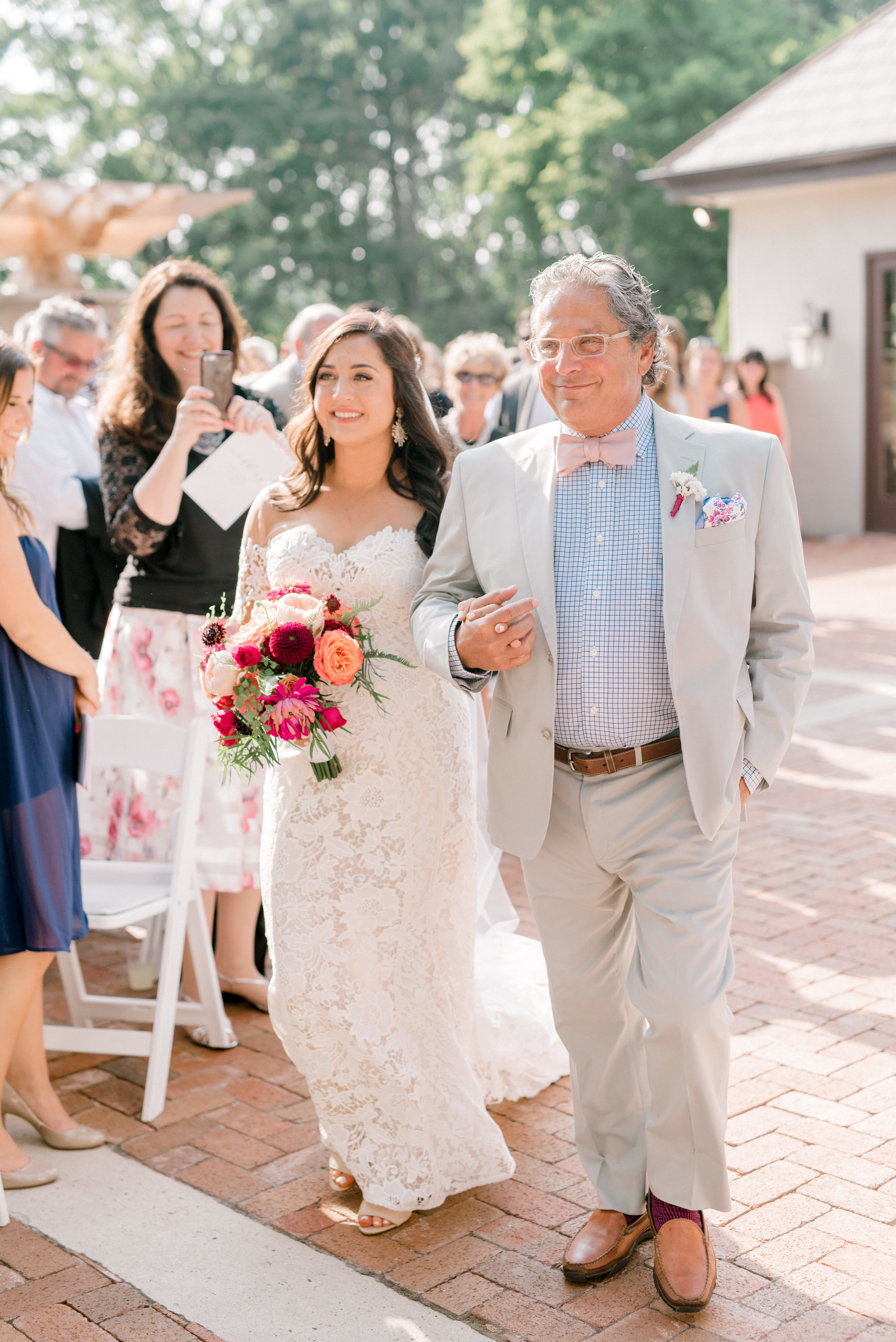 An emotional moment as Lindsey walks down the aisle with her dad for her bright and modern summer wedding day at Hotel du Village.