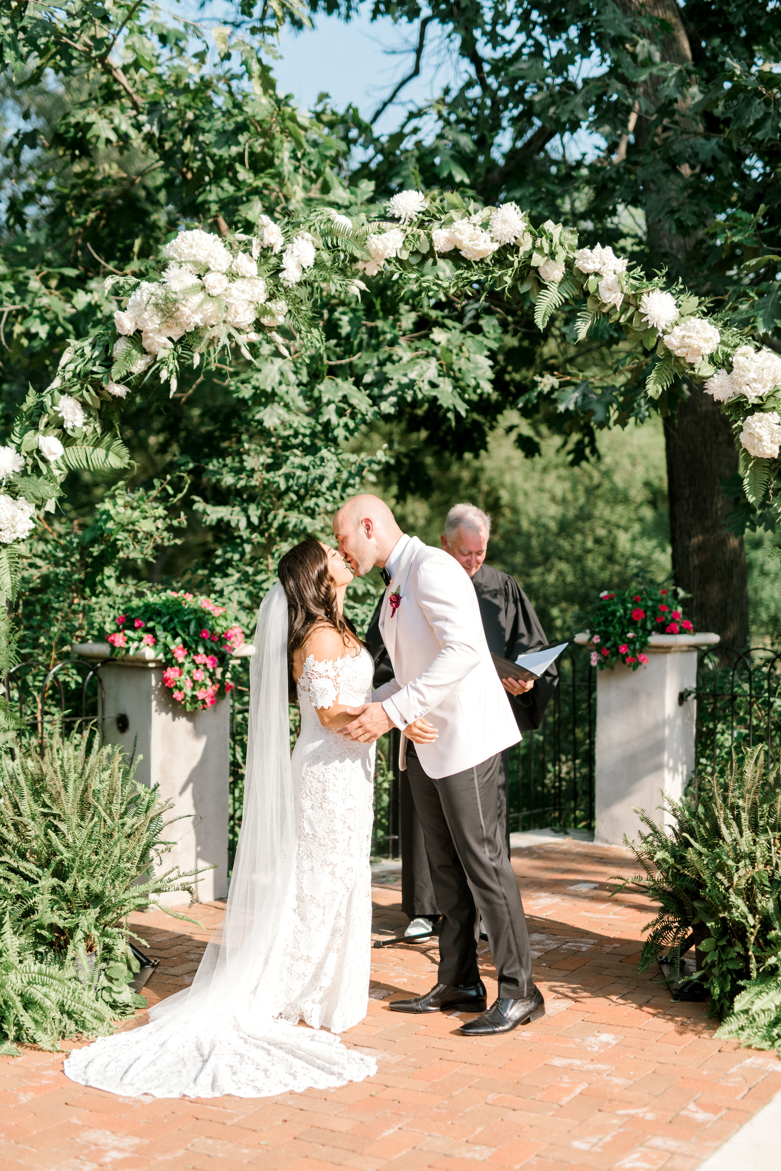 Lindsey and James share their first kiss under the white floral arch for their modern and bright summer wedding day at Hotel du Village.