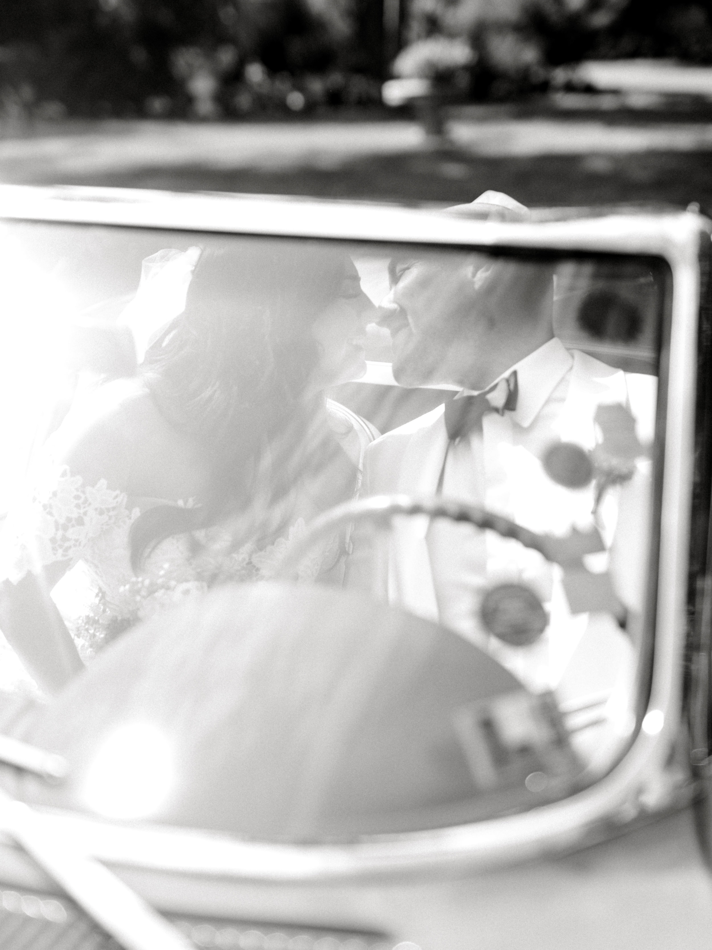 Kissing in the car, we love a classic car to make for a grand statement on your wedding day.