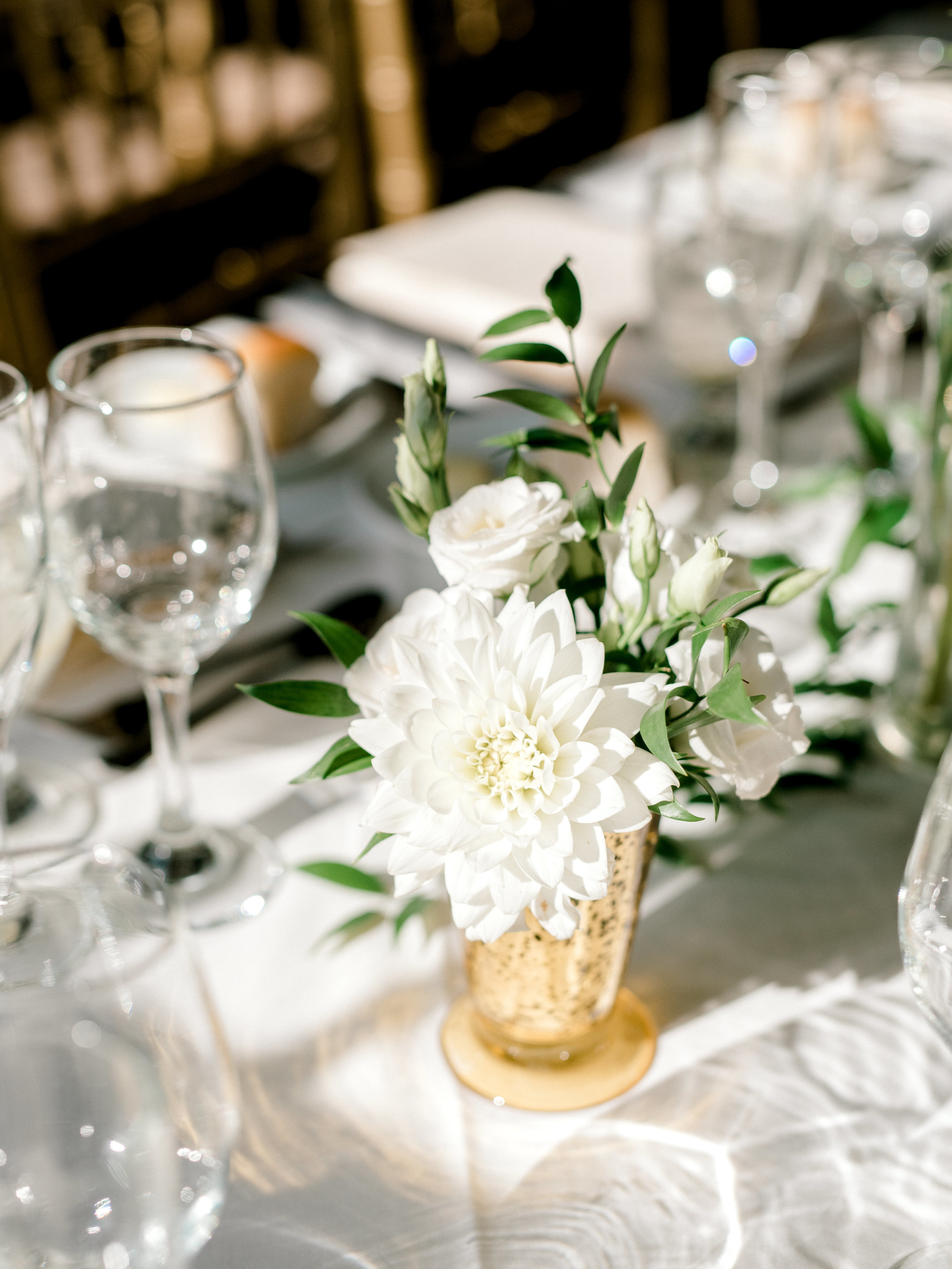 This bursting white dahlia in a gold vase adds a bright touch to the tablescape of this modern summer wedding at Hotel du Village.