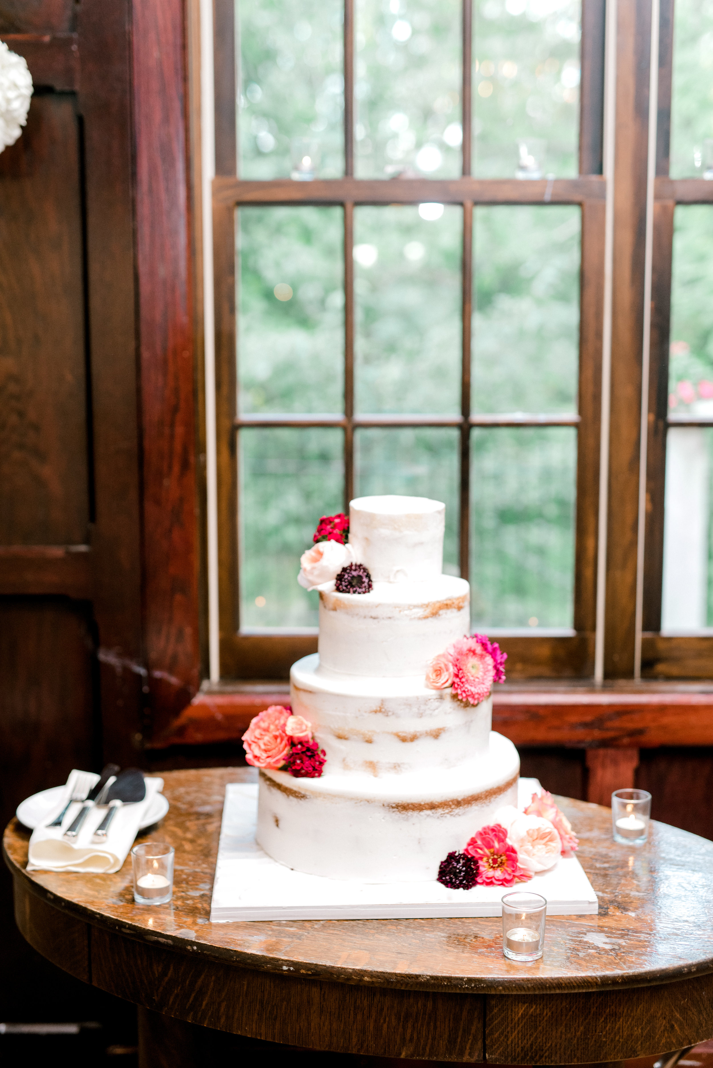 This simple naked cake with pops of pink flowers at Hotel du Village has us dreaming of modern summer weddings.