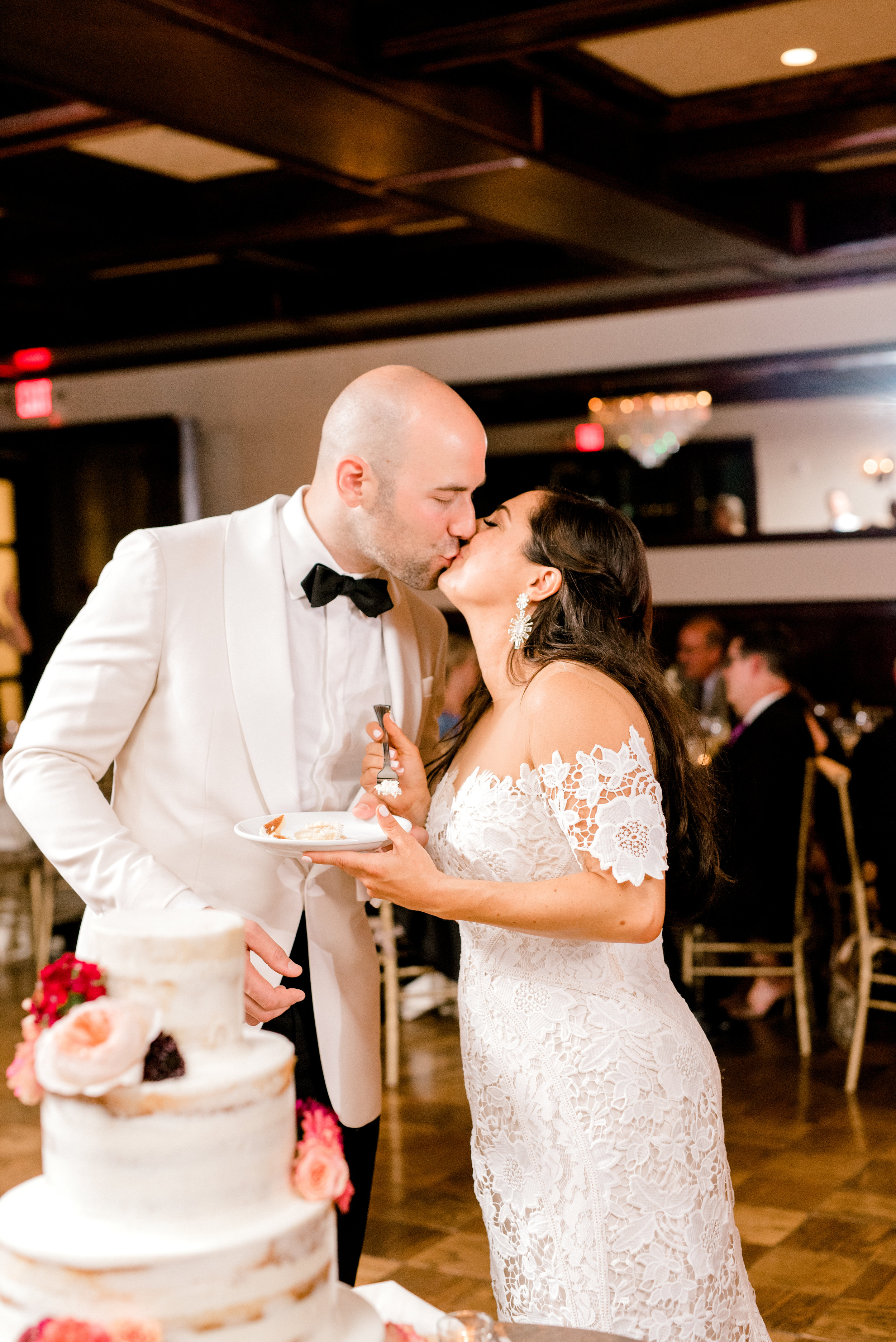 Modern and elegant, these two share a kiss after cutting the cake at their summer Hotel du Village wedding.