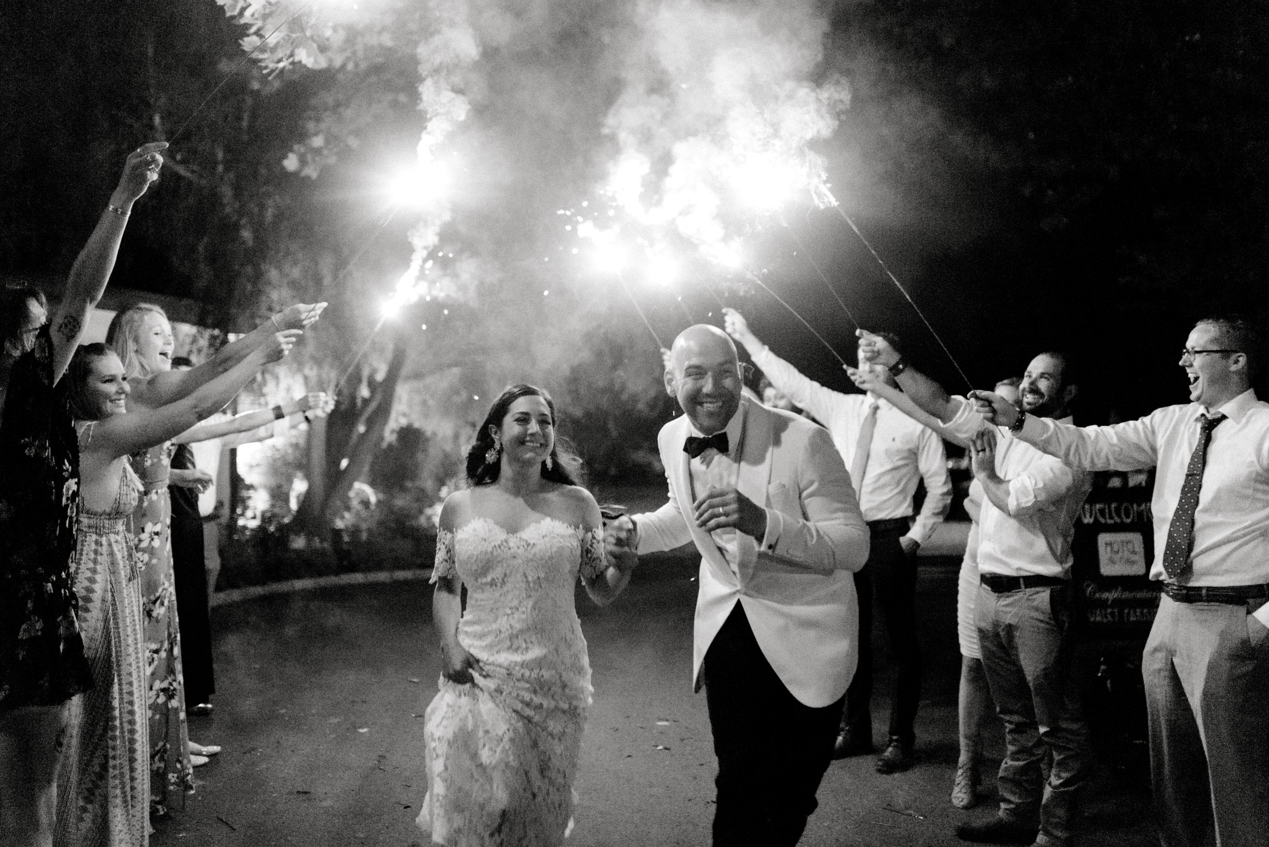 Happy as can be, Lindsey and James run through a line of sparklers to celebrate their amazing modern and bright summer wedding day at Hotel du Village.