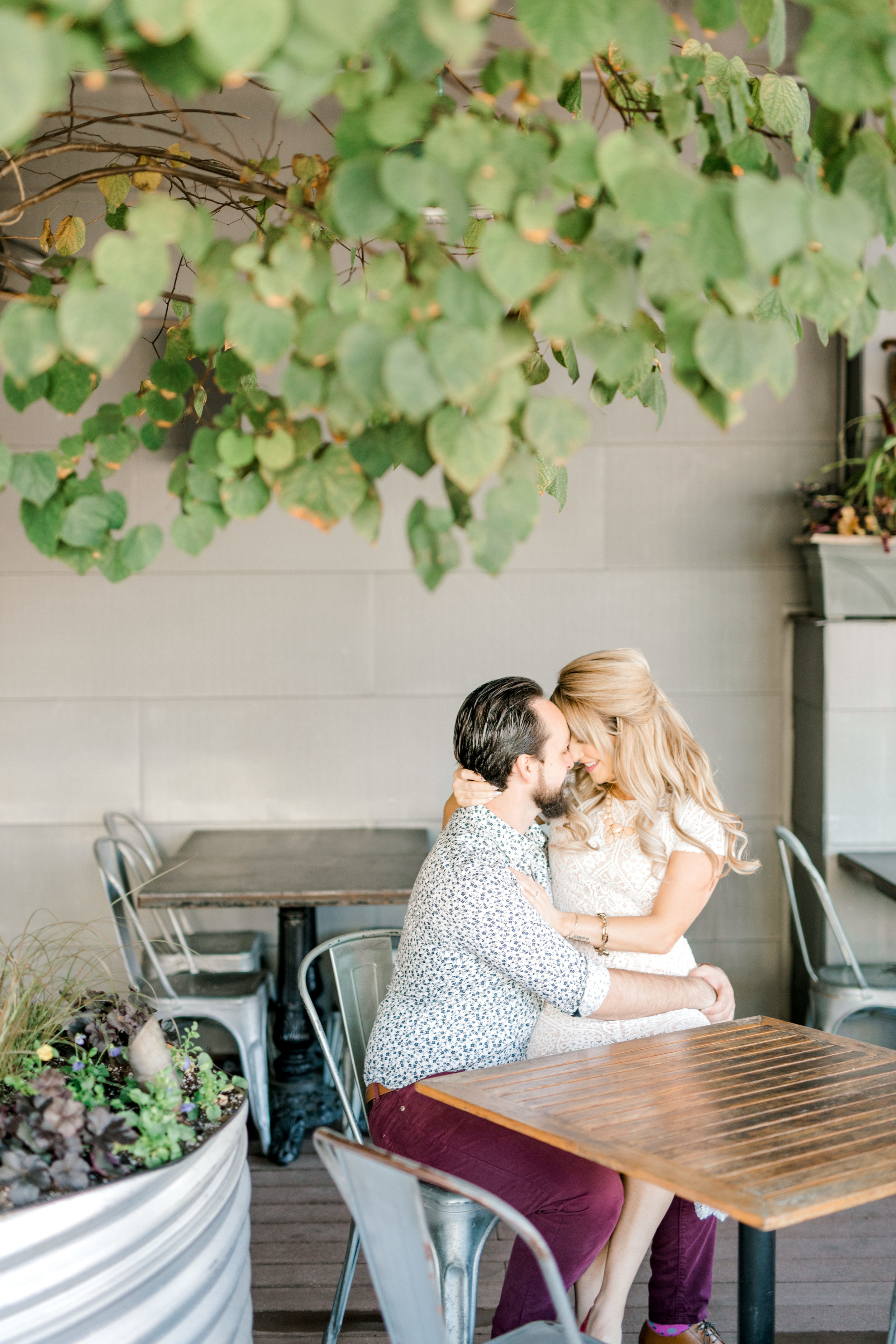 Nikki gets romantic and sits on Dale's lap for their bright fall engagement session on the patio at the Revolution House in Old City, Philadelphia.