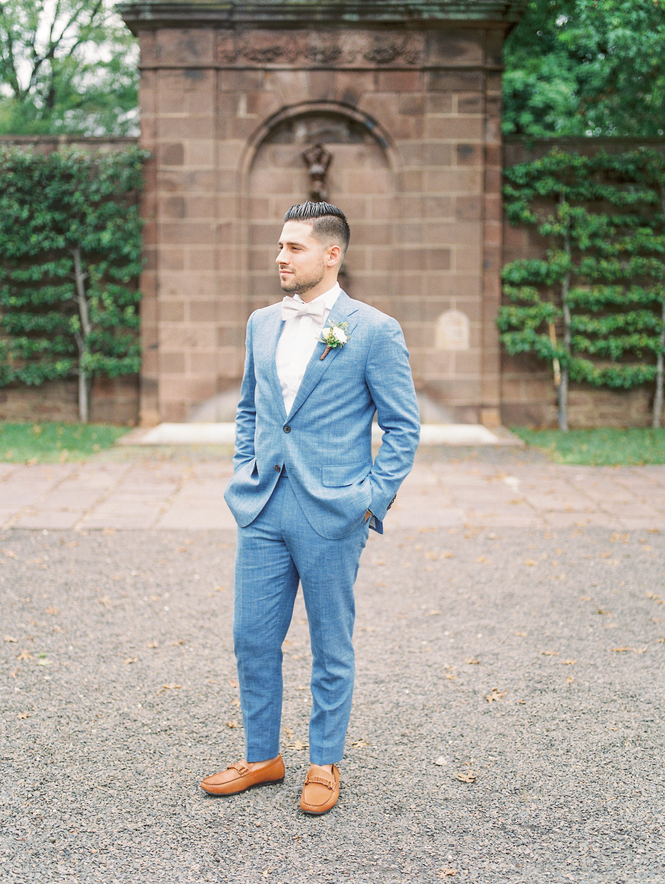 This groom's light blue suit paired with brown leather loafers and white bowtie made him one stylish and timeless looking man for his bright boho chic Tyler Gardens wedding in Bucks County