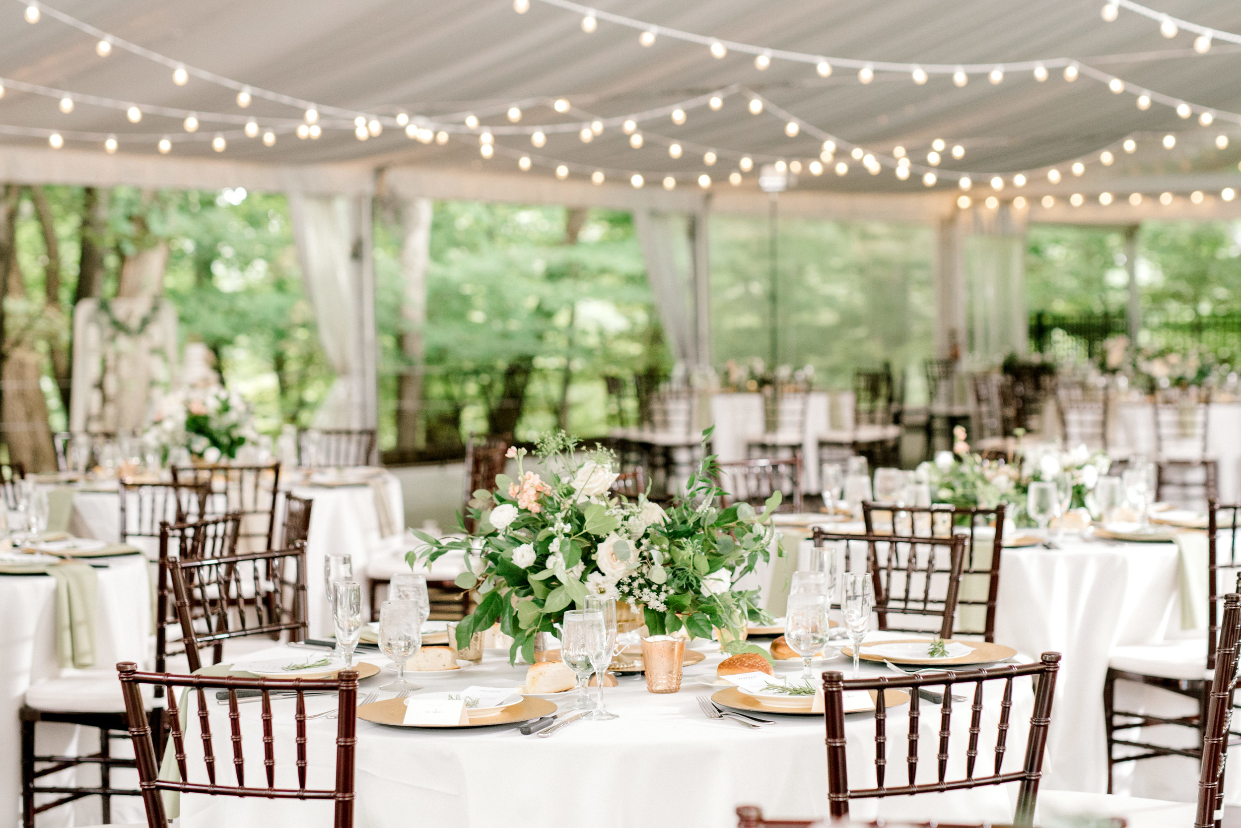 Classic whites and greens with a bit of whimsy in string lights pulled together the reception tent for this bright boho chic Tyler Gardens wedding in Bucks County.