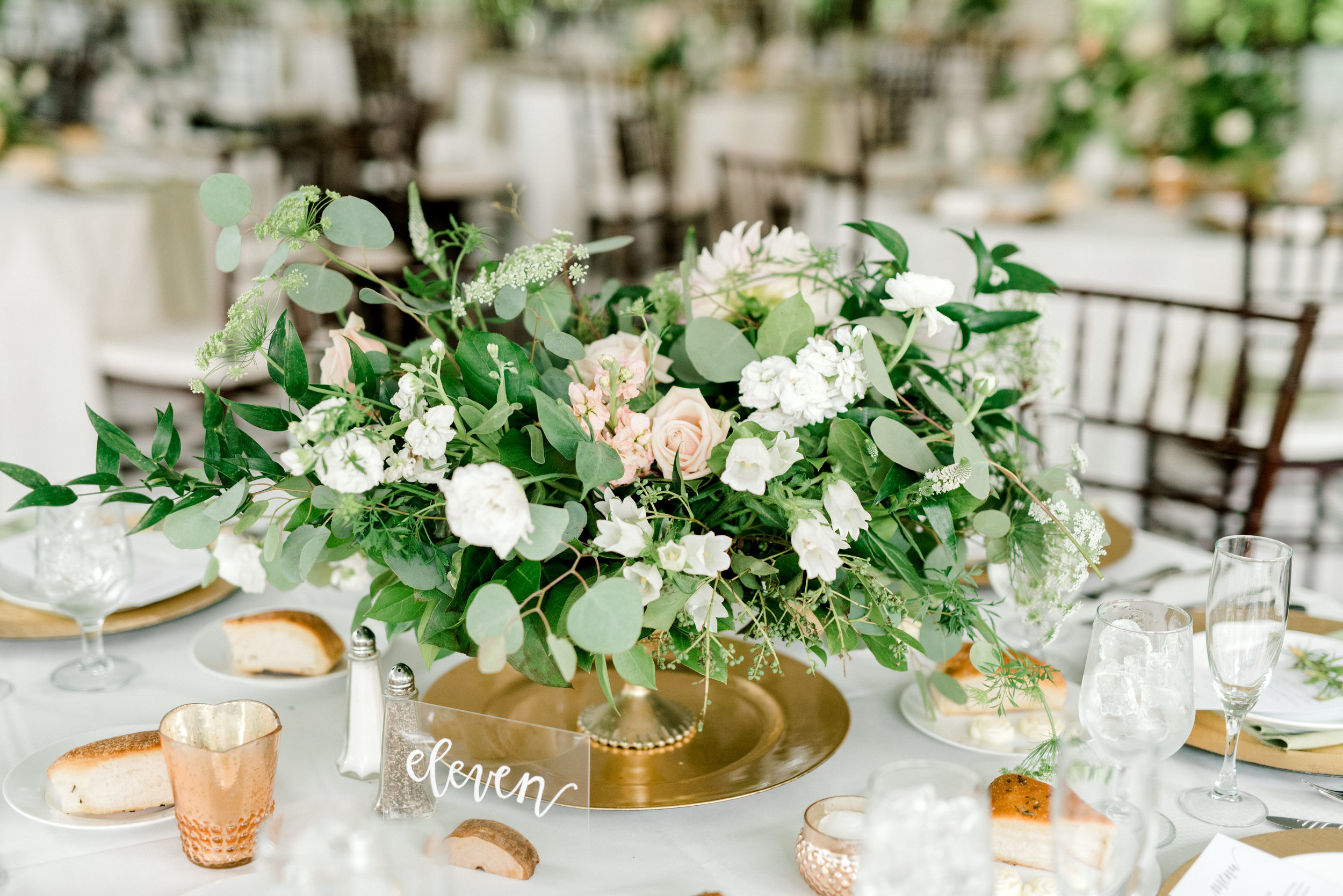 Wild green centerpieces with white and blush flowers add a bit of nature to this white and gold reception at this bright boho chic Tyler Gardens wedding in Bucks County