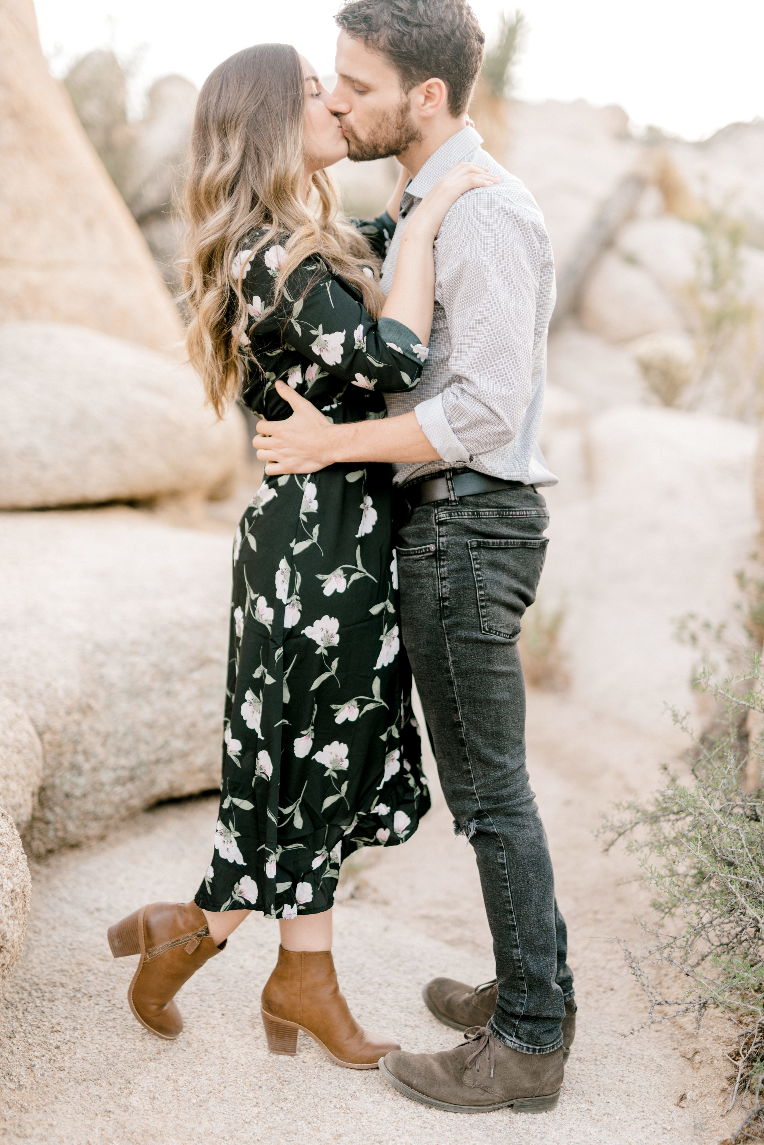 Smooches for this stylish boho couple at their free-spirited desert engagement session in Joshue Tree