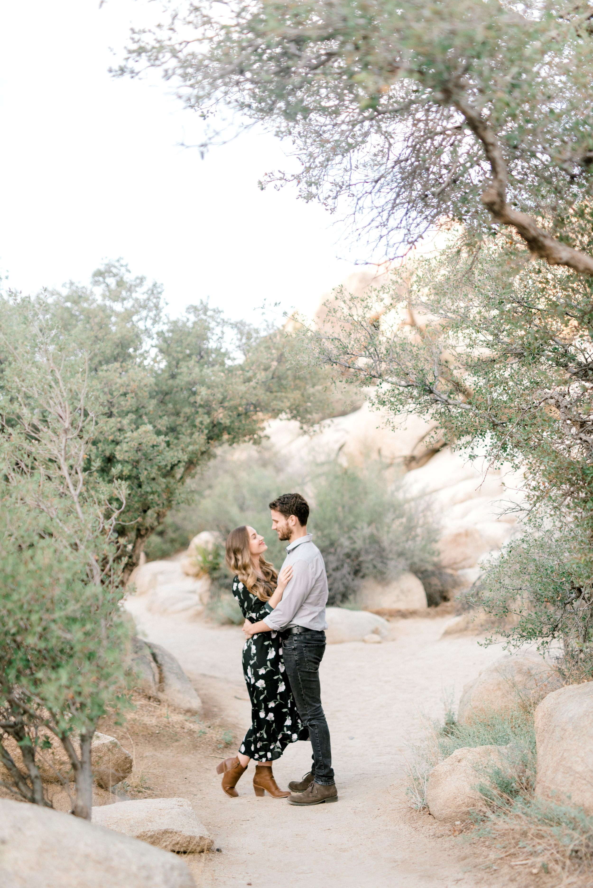 Jenna and Sam are perfectly framed in the soft green trees for their  free-spirited desert engagement session in Joshue Tree