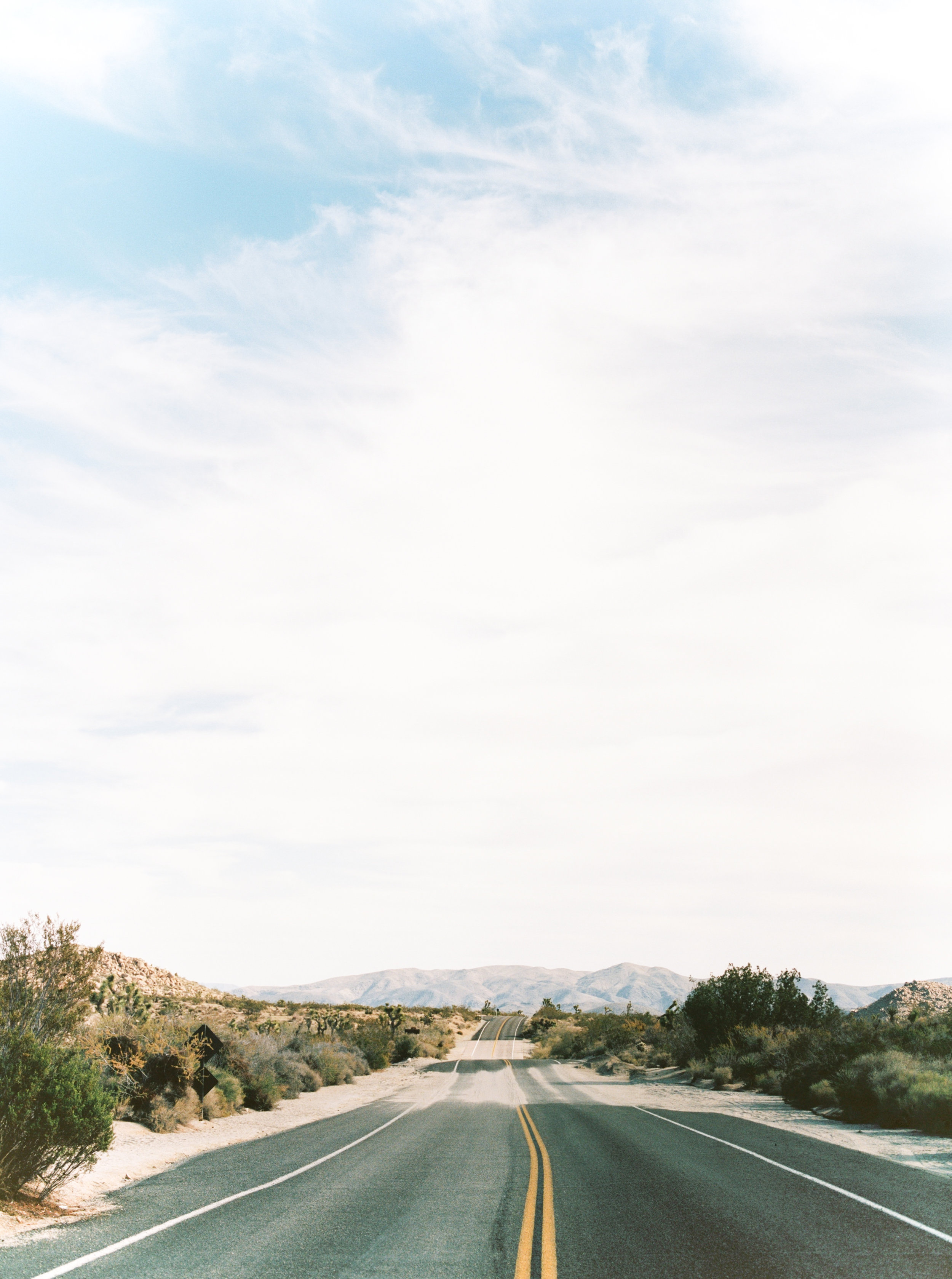 We just want to head off down the road toward those mountains in the distance at this free-spirited desert engagement session in Joshue Tree