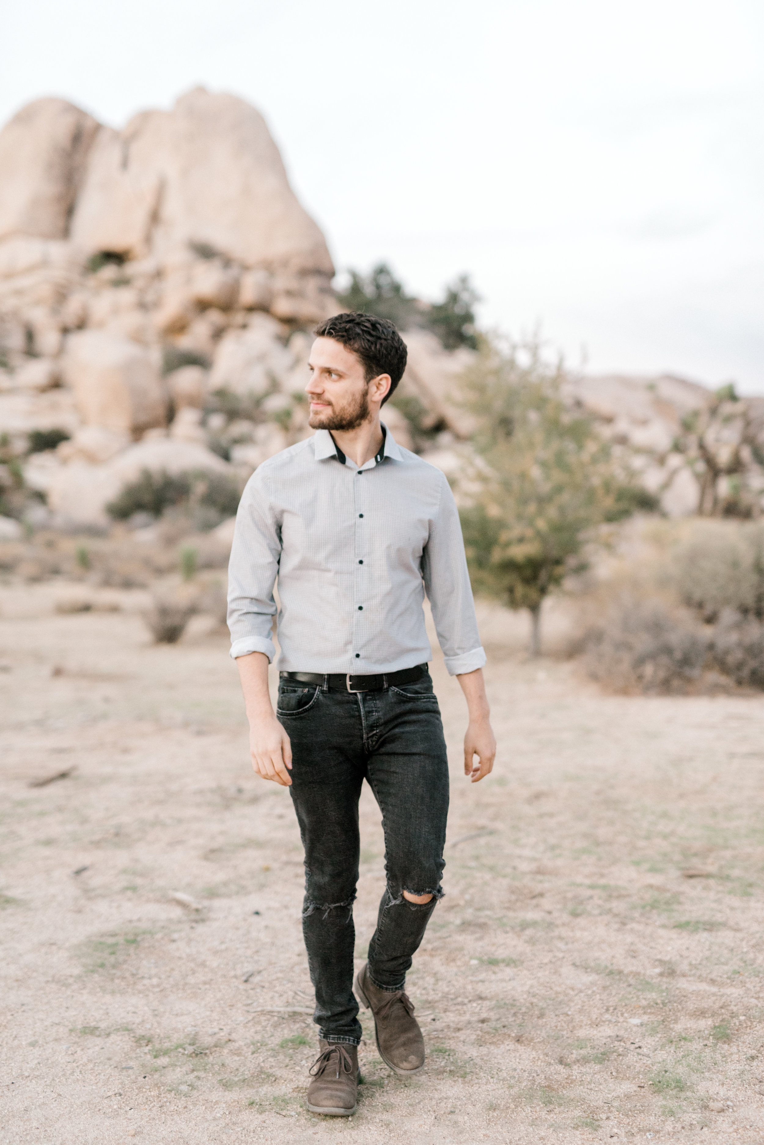 Sam's edgy torn jeans paired with a clean cut oxford made this boho look pulled together for their free-spirited desert engagement session in Joshue Tree