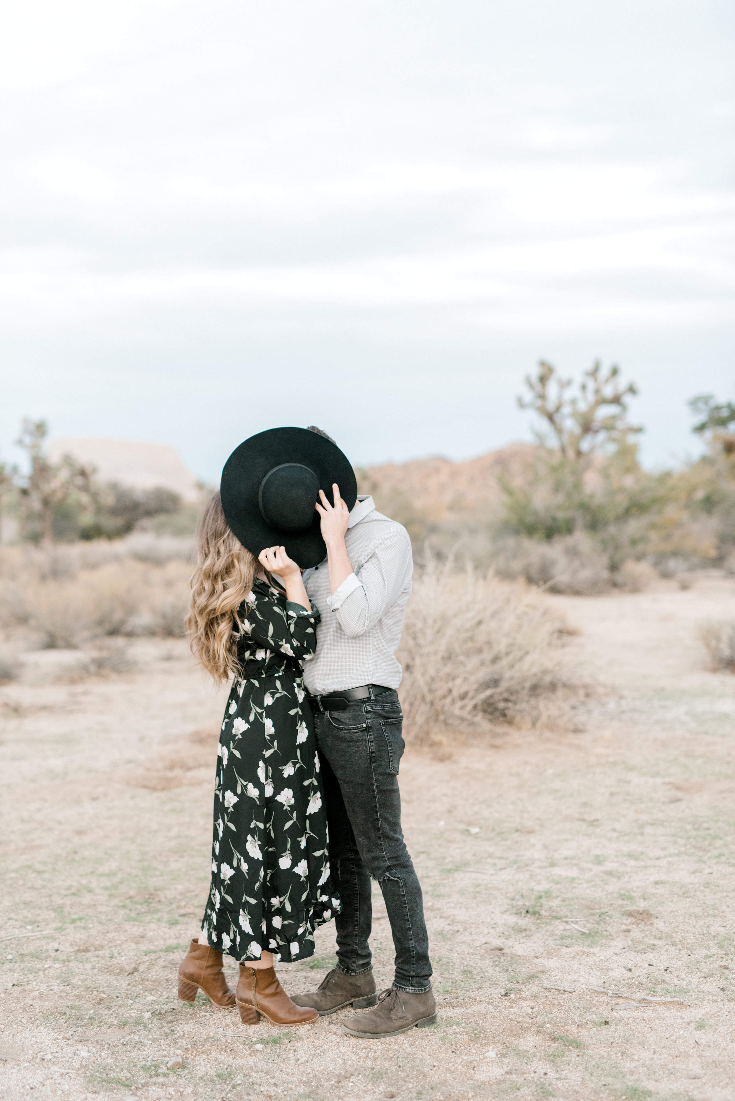 A cute moment as these two share a kiss hidden behind Jenna's floppy boho hat for their free-spirited desert engagement session in Joshue Tree