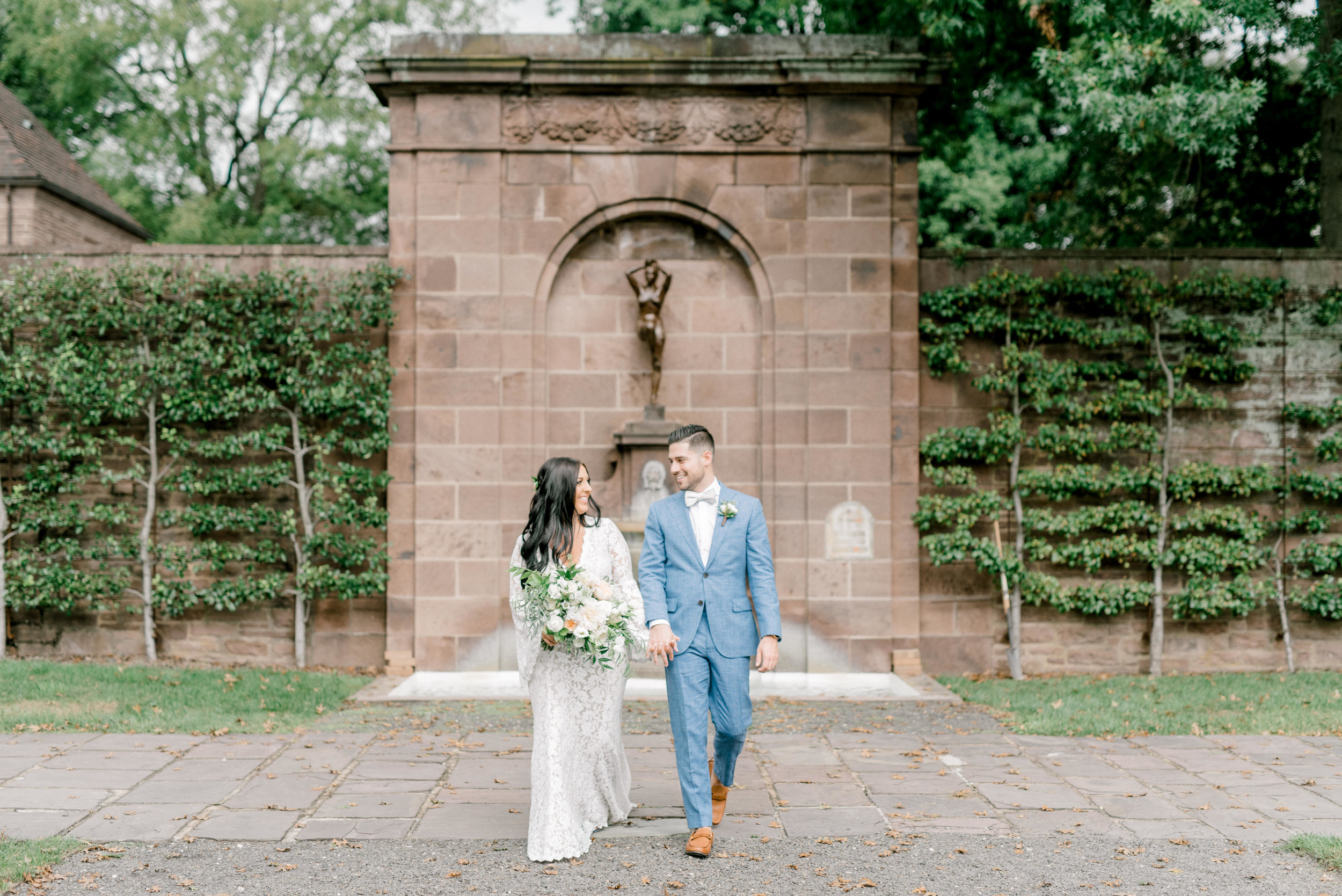 We absolutely adore the European vibes from these stone walls and arches and statues in this garden at this bright boho chic Tyler Gardens wedding in Bucks County