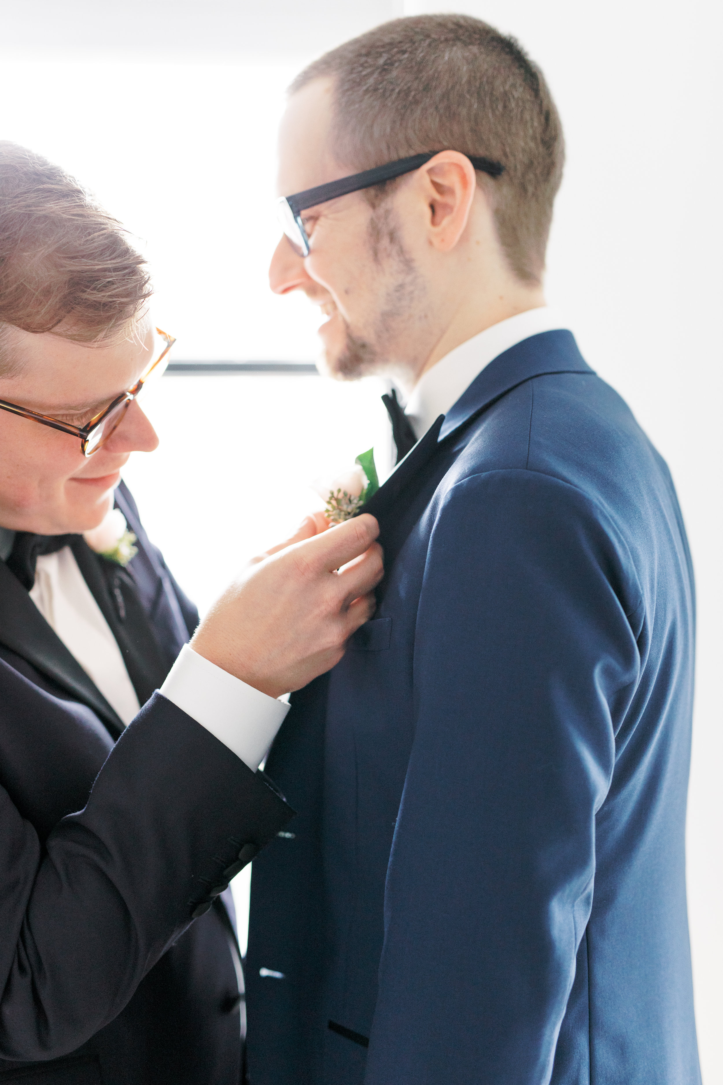 two grooms getting ready together on their Philadelphia wedding day putting on boutonnière