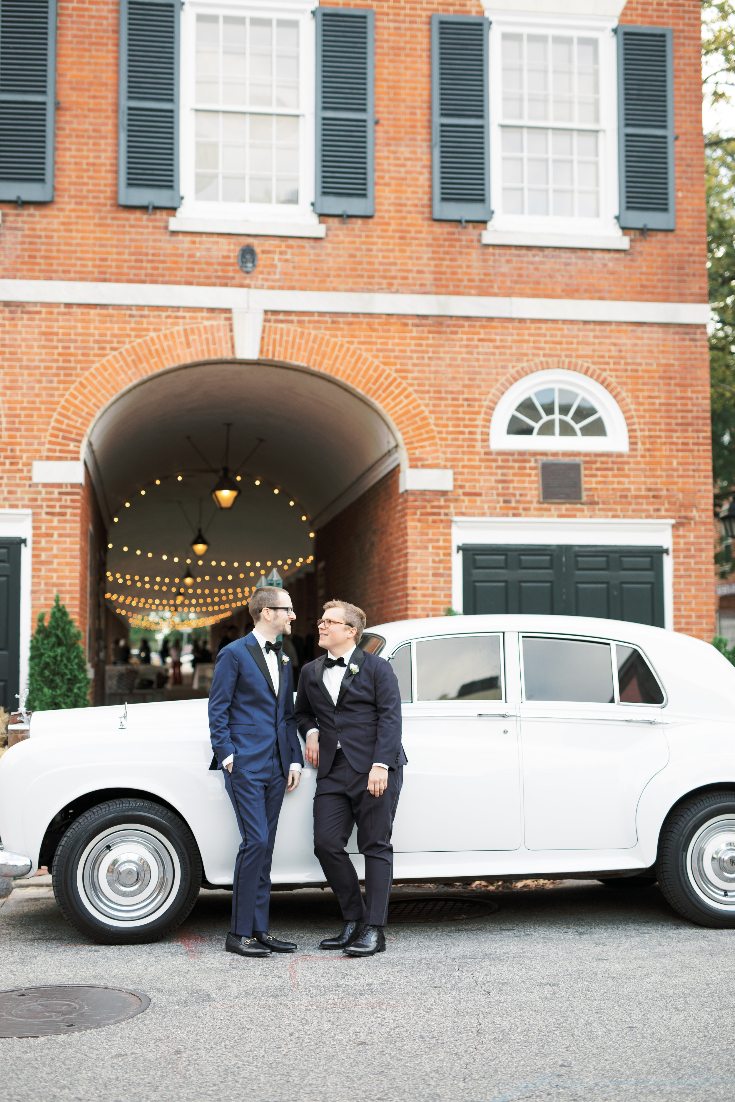 same sex wedding, two grooms with glasses on their Philadelphia wedding day with a Rolls Royce in classic Headhouse Square