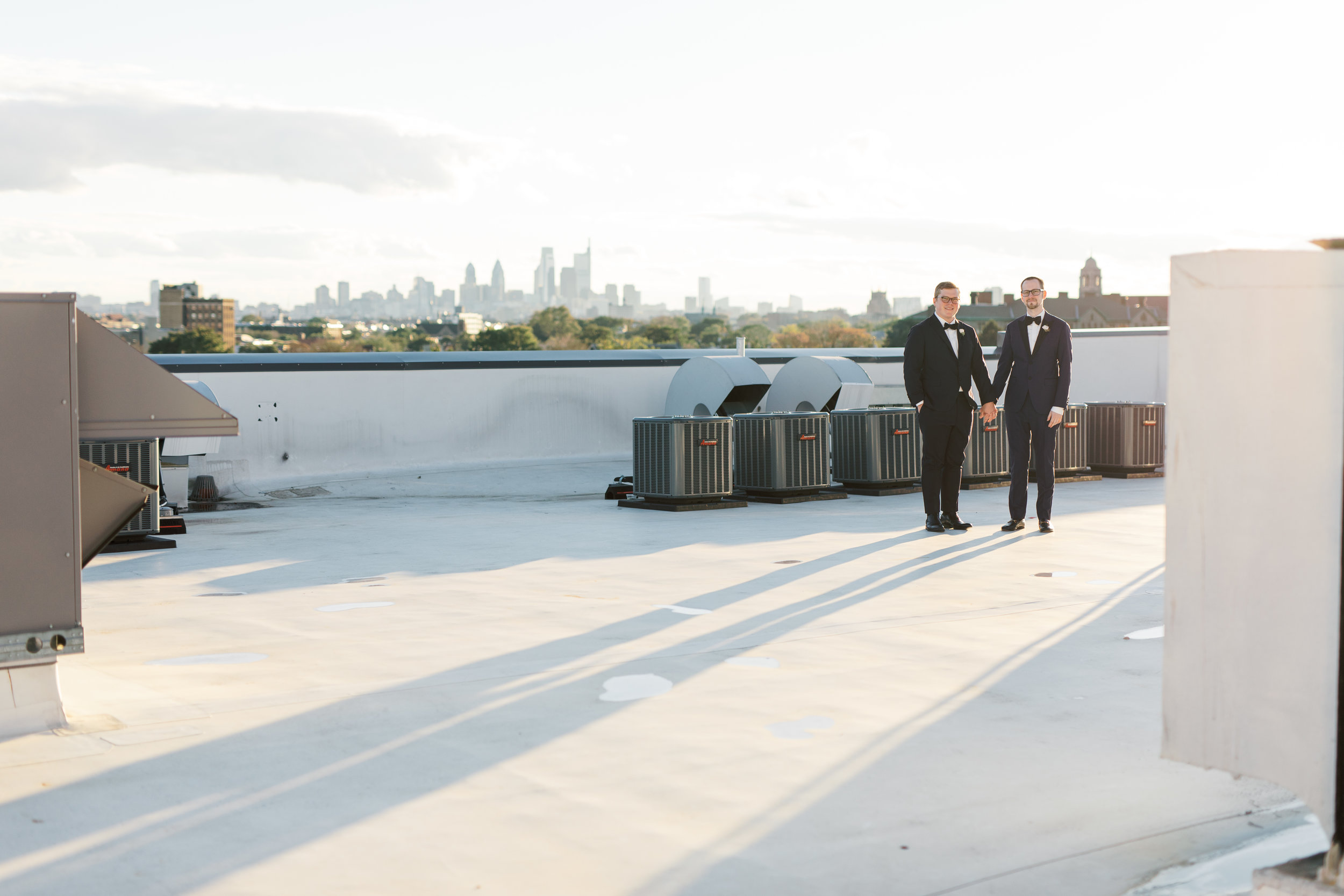 industrial and modern rooftop wedding venue, FAME, in Philadelphia with skyline view with two grooms