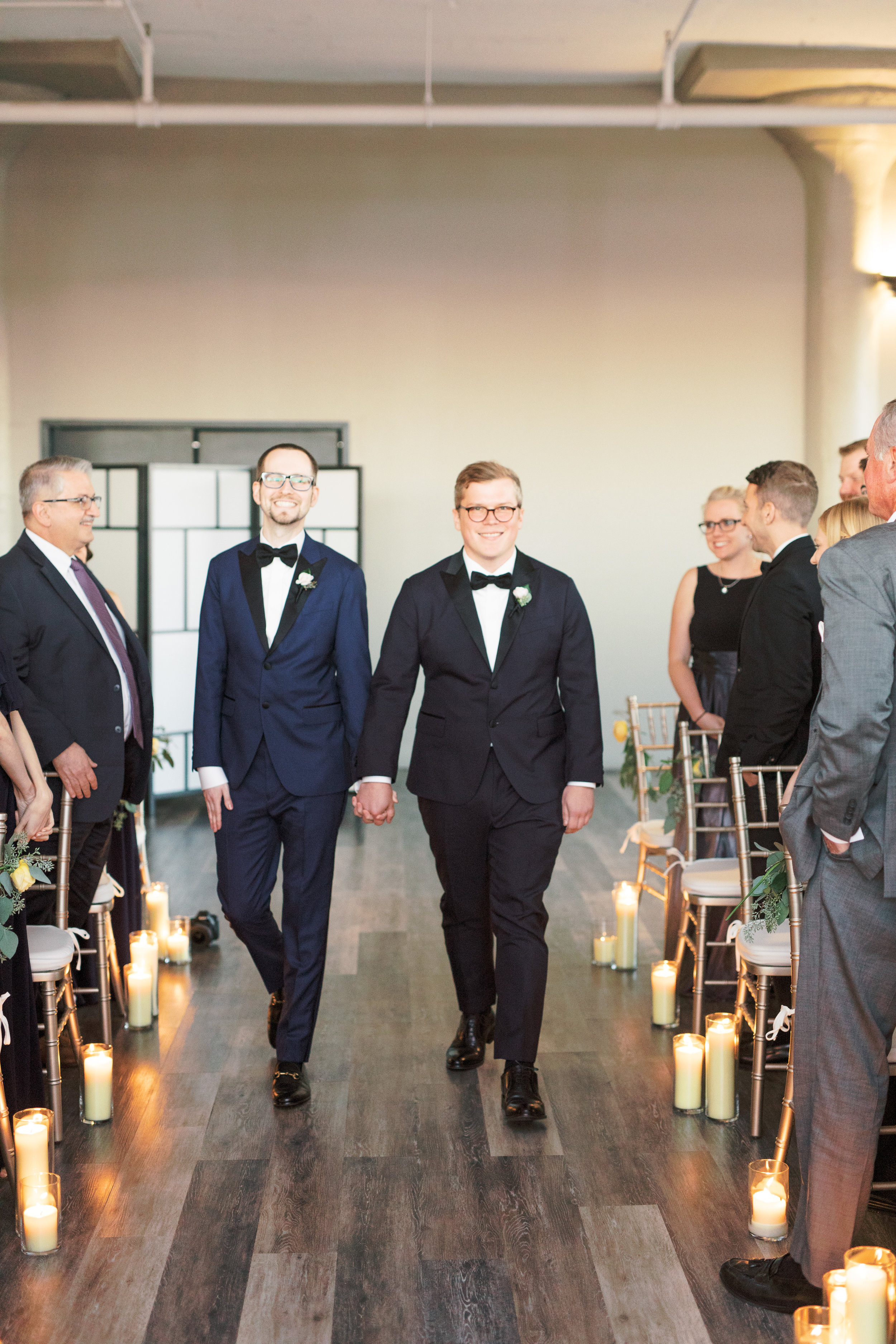 two grooms walking down the aisle together at FAME, industrial and modern Philadelphia venue