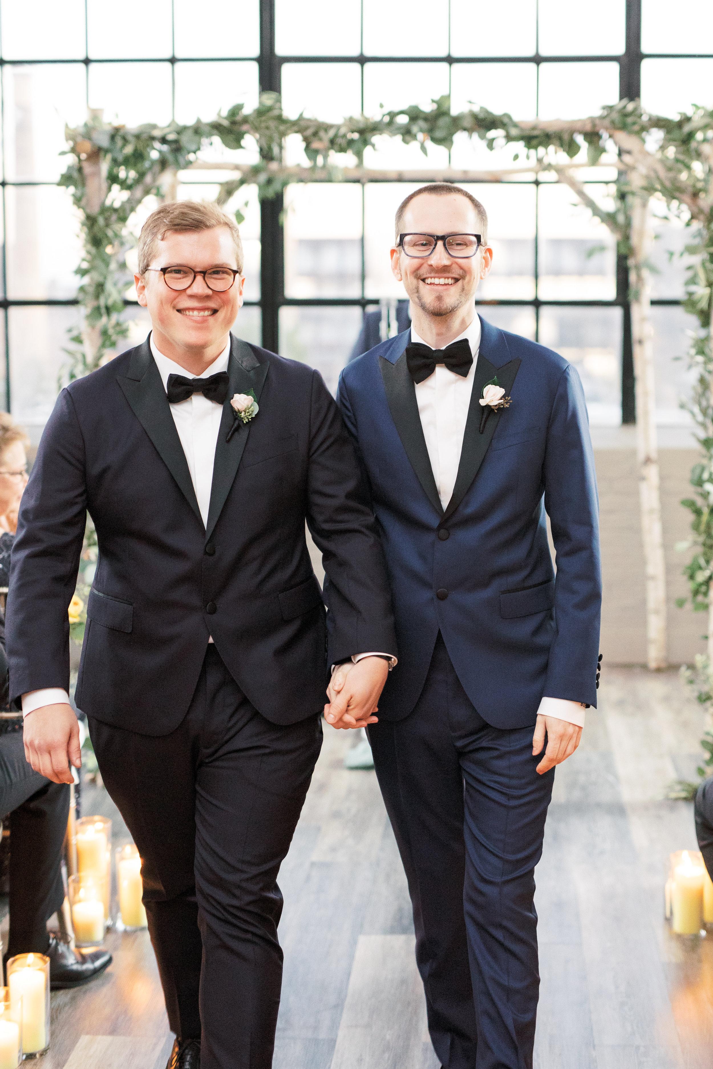 same sex wedding ceremony at FAME, industrial and modern warehouse Philadelphia wedding venue, precessing as husbands