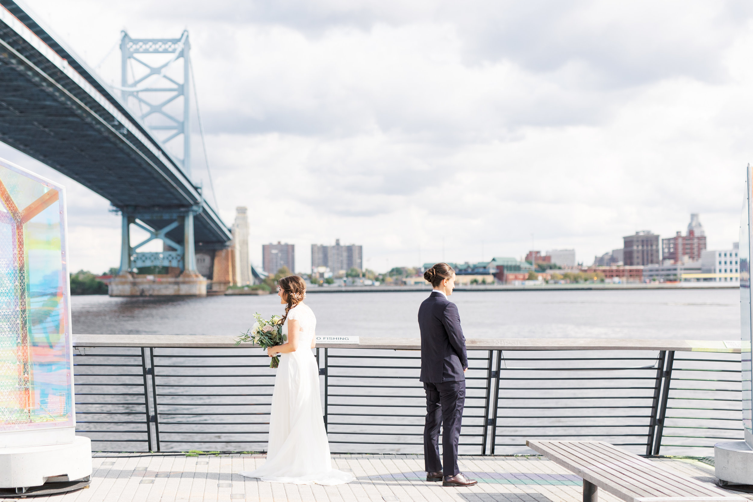 At Race Street Pier, just in front of the Benjamin Franklin Bridge, Missy and Dani stand back to back just moments before their first look at their modern and elegant old city Philadelphia wedding at Power Plant Productions. Power Plant Production wedding photographer