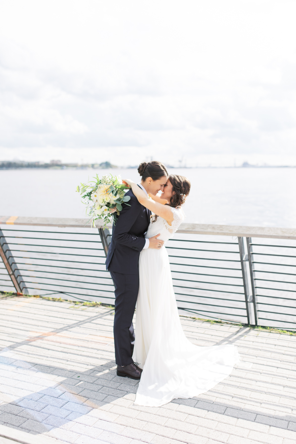 The happy couple share a kiss on Race Street Pier overlooking the Delaware River for their modern and elegant old city Philadelphia Power Plant Productions wedding. Power Plant Production wedding photographer