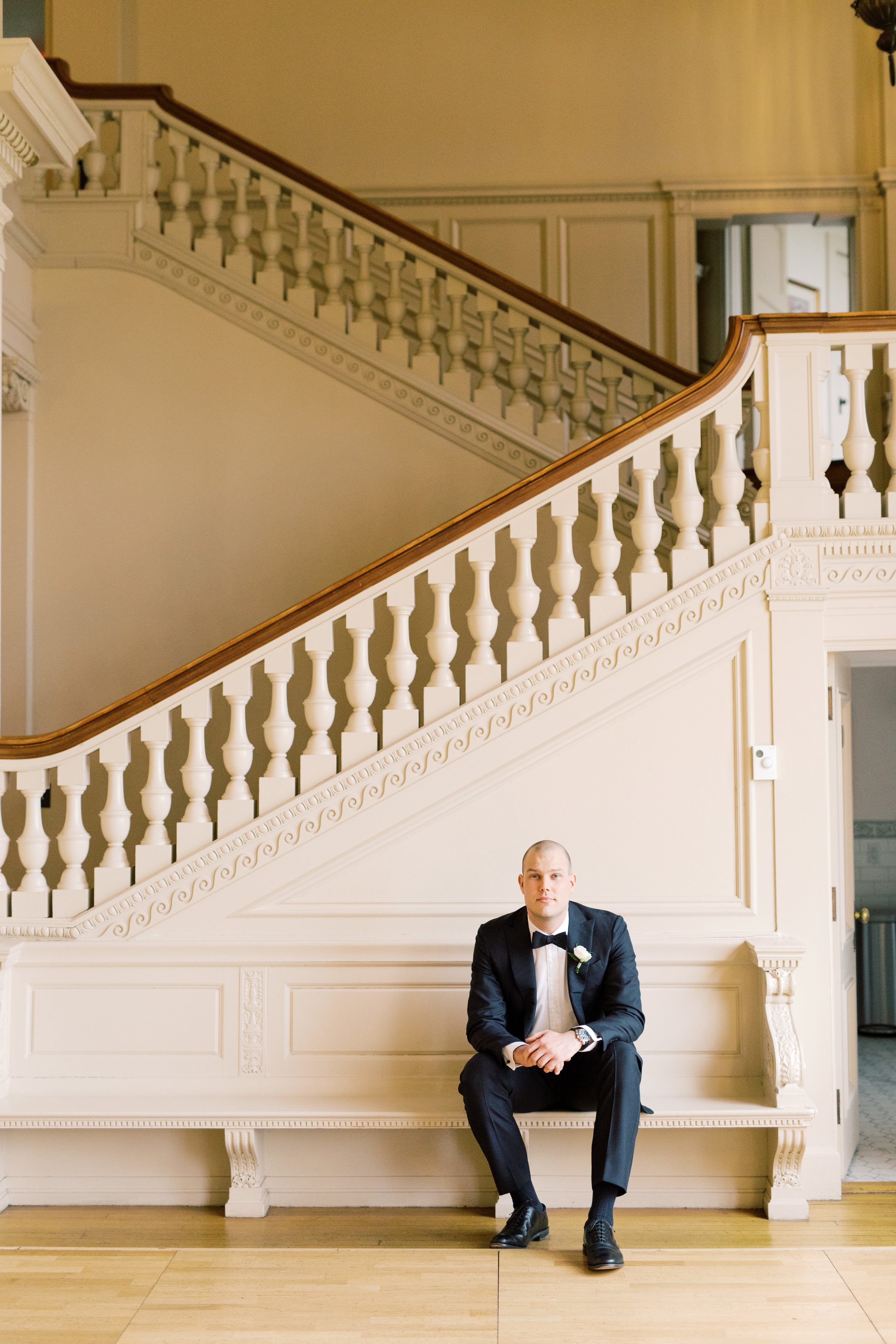 The grand staircase made for an impactful statement for portraits with this classic groom from this romantic and classic wedding day for their french inspired green and white Cairnwood Estate wedding