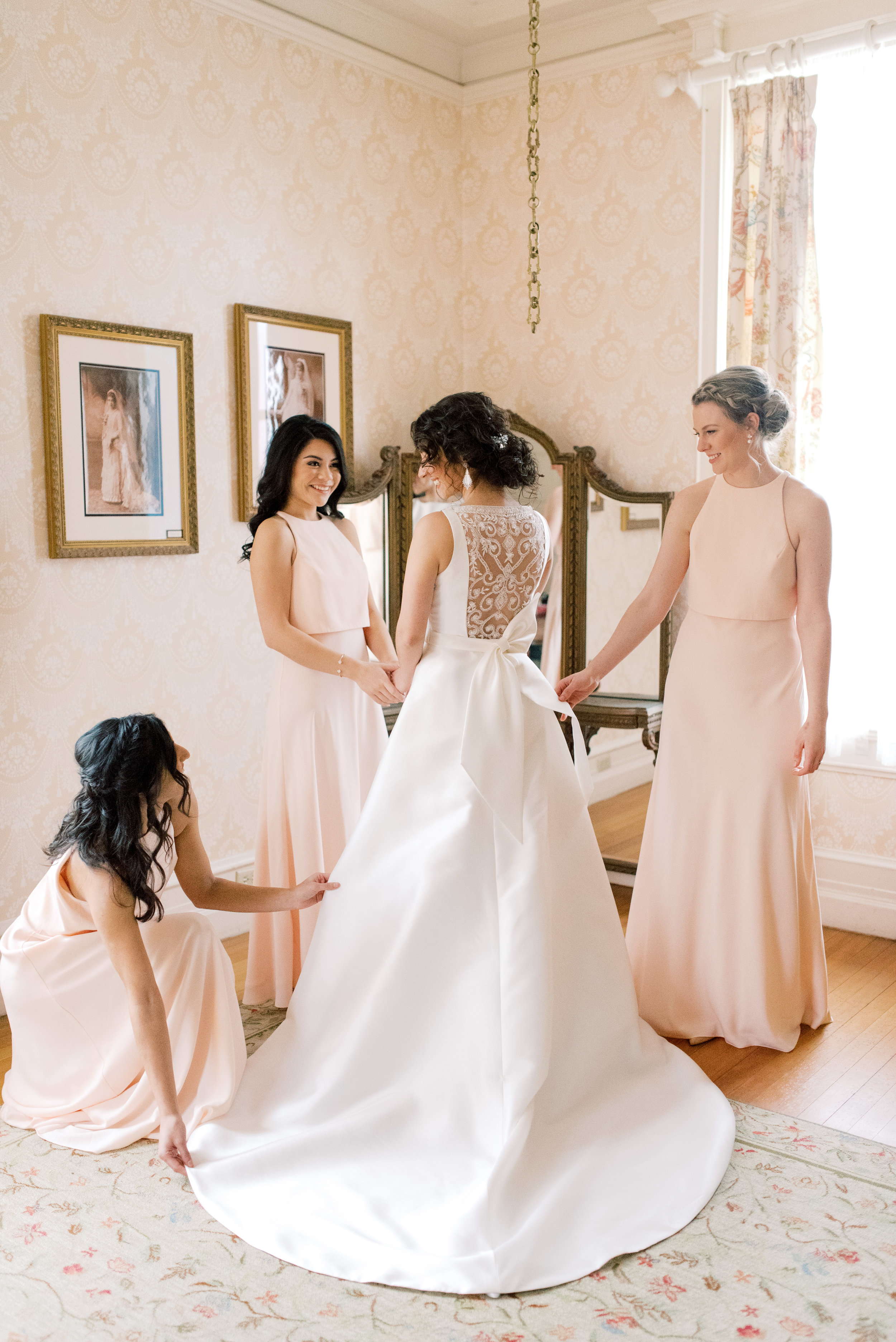 We loved the way these blush pink bridesmaids dresses gave a feminine touch to this get ready photograph of our beautiful bride getting into her modern a-line dress for her romantic and classic wedding day for their french inspired green and white Cairnwood Estate wedding
