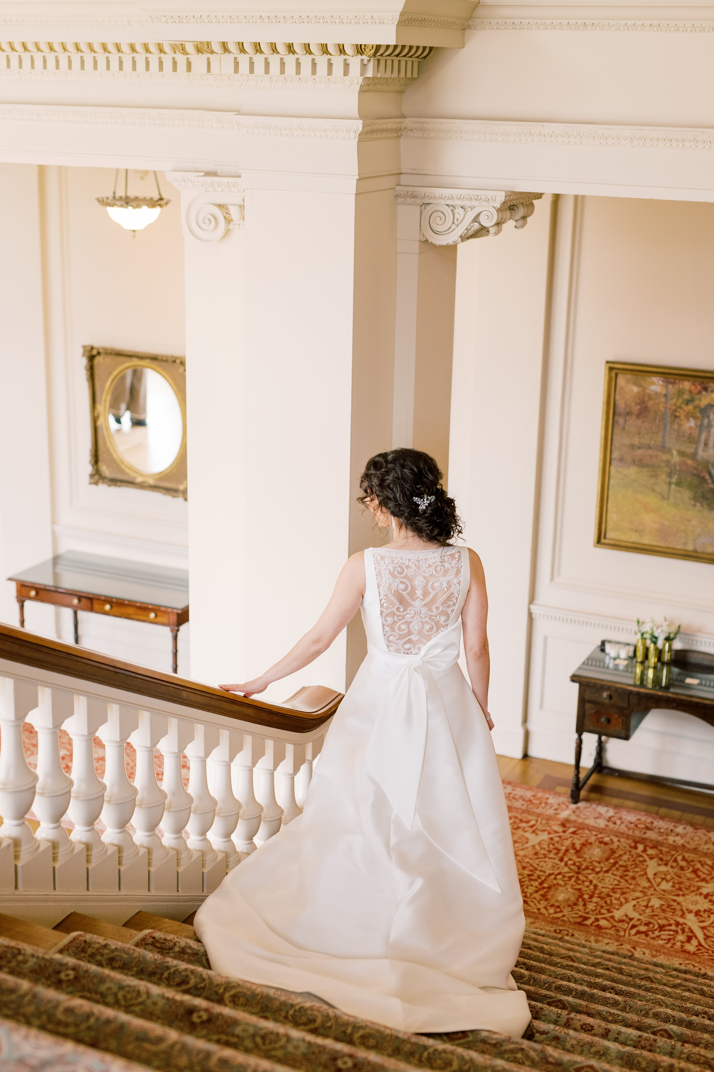 Our bride heads down the grand staircase as she is about to see her groom for the first time at their romantic and classic wedding day for their french inspired green and white Cairnwood Estate wedding