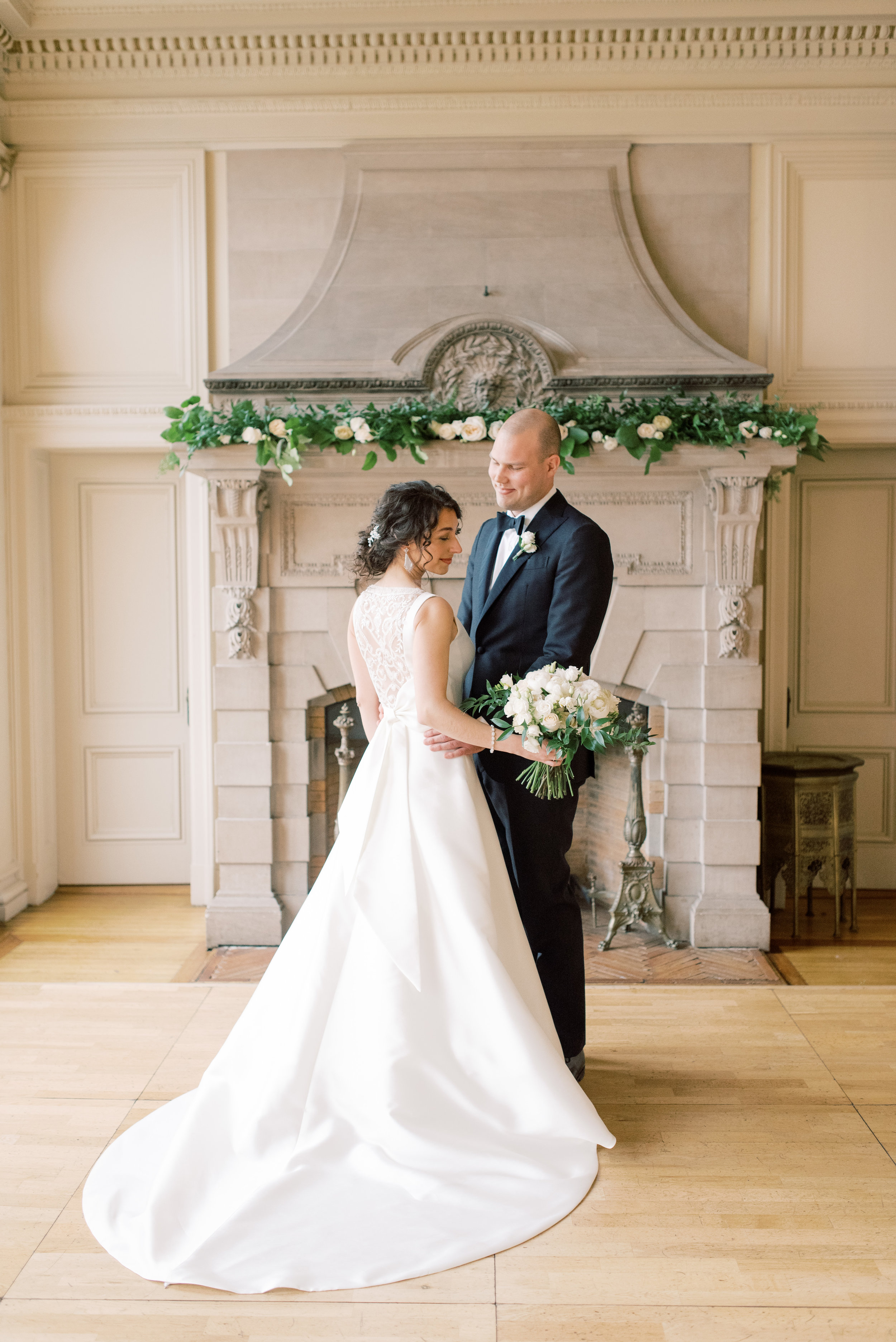 We so love this classic bride and groom standing in front this unique french stone fireplace at their romantic and classic wedding day for their french inspired green and white Cairnwood Estate wedding