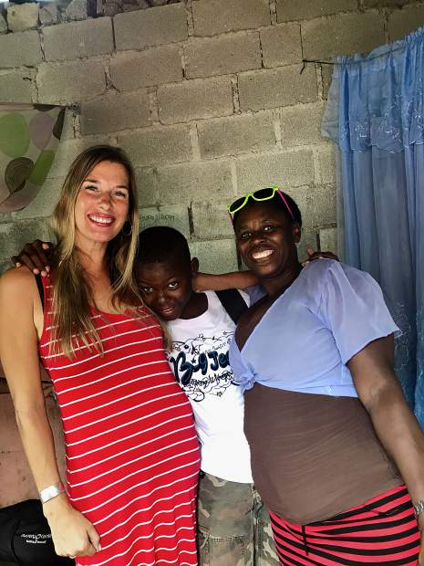 Jonas poses for a photo with Jaci and his mother, Nelta Mondesir, in front of their house.