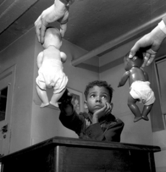 Image from a 1940 study by Clark and Clark, where a child is choosing to play with a white doll over a black doll.