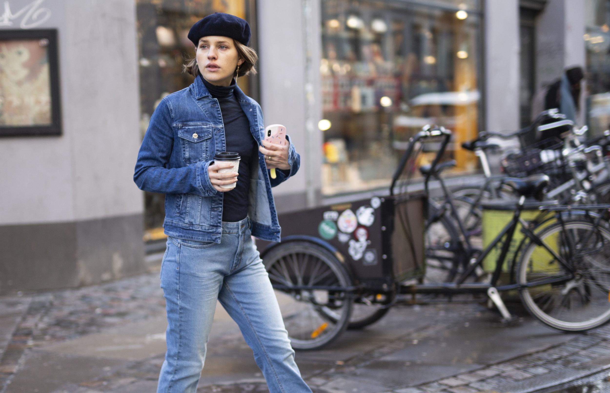 Julie Blichfeld on the streets of Copenhagen wearing a denim set from Denim Hunter with a coffee togo