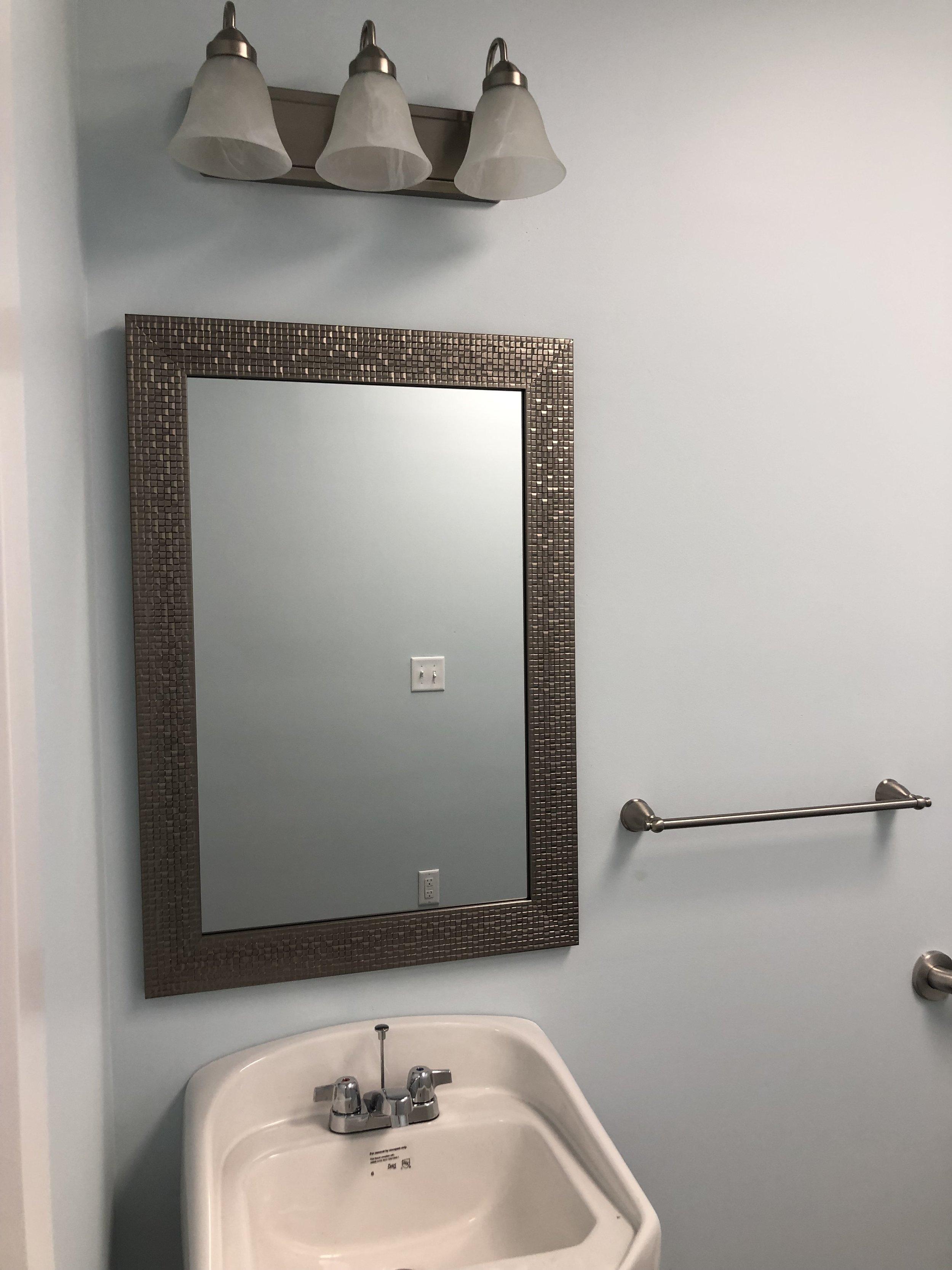 Bathroom sink, mirror, and vanity light in place.