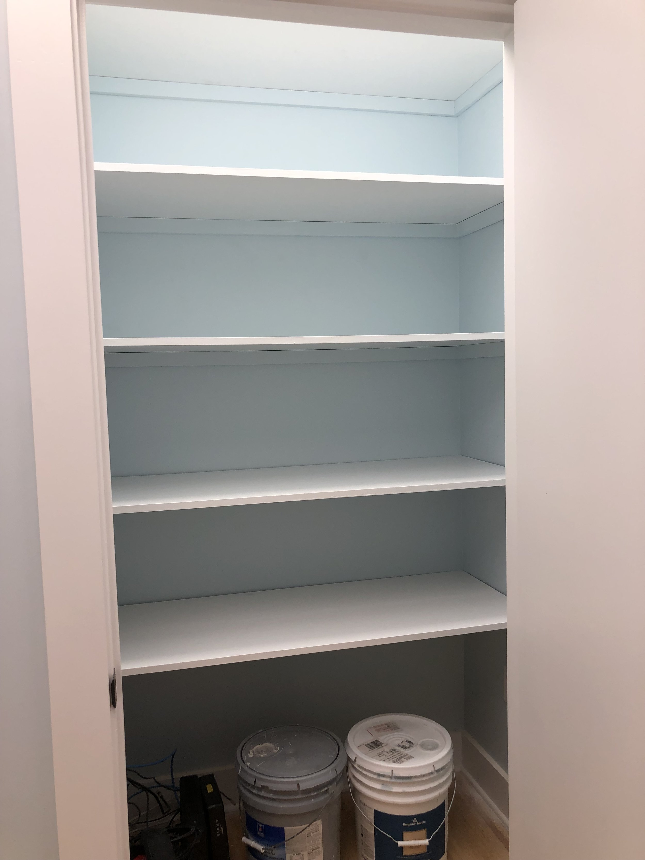 Supply closet nearing completion with shelves installed.