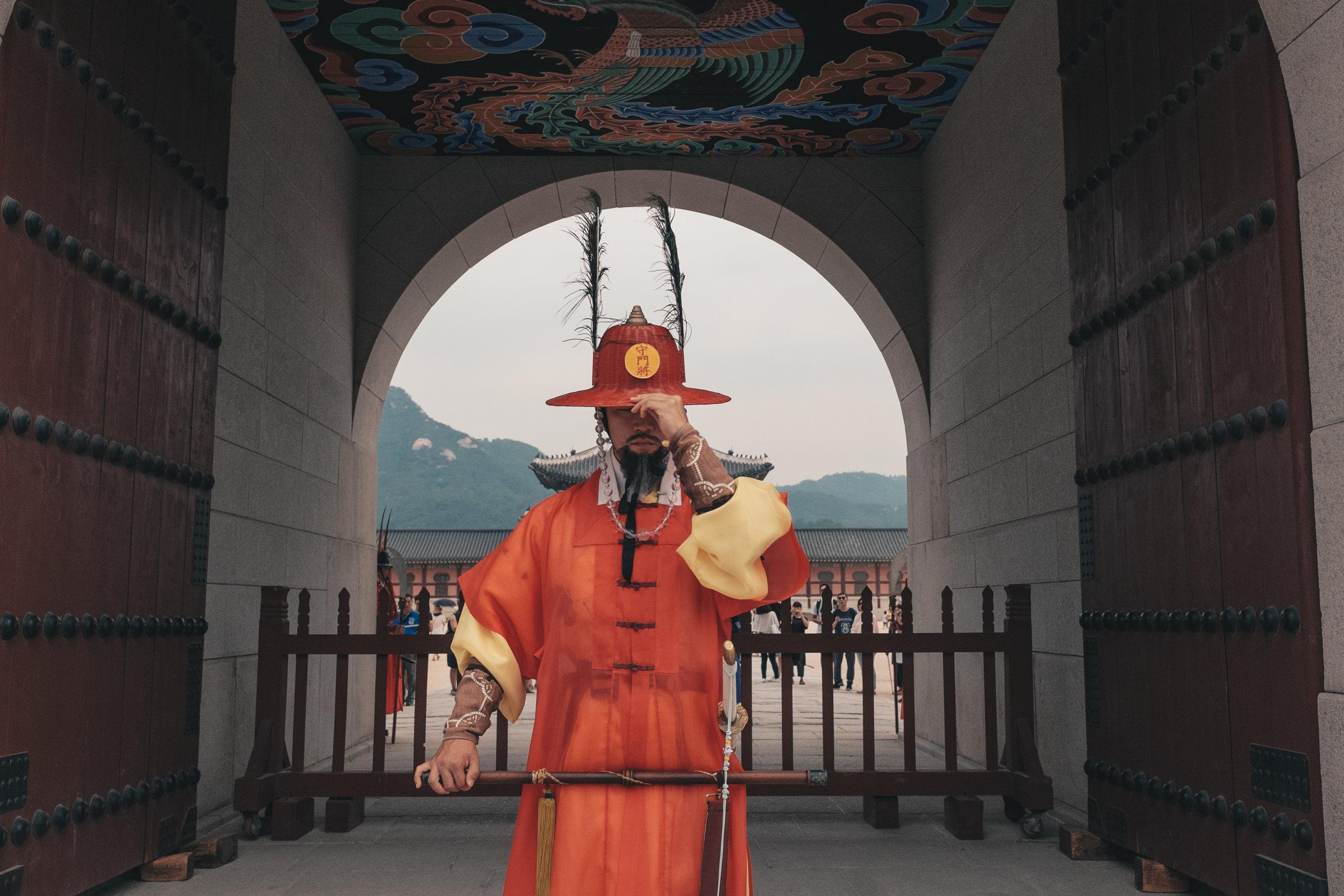 A royal guard posing for a picture at Seoul's Gyeongbukgung Palace