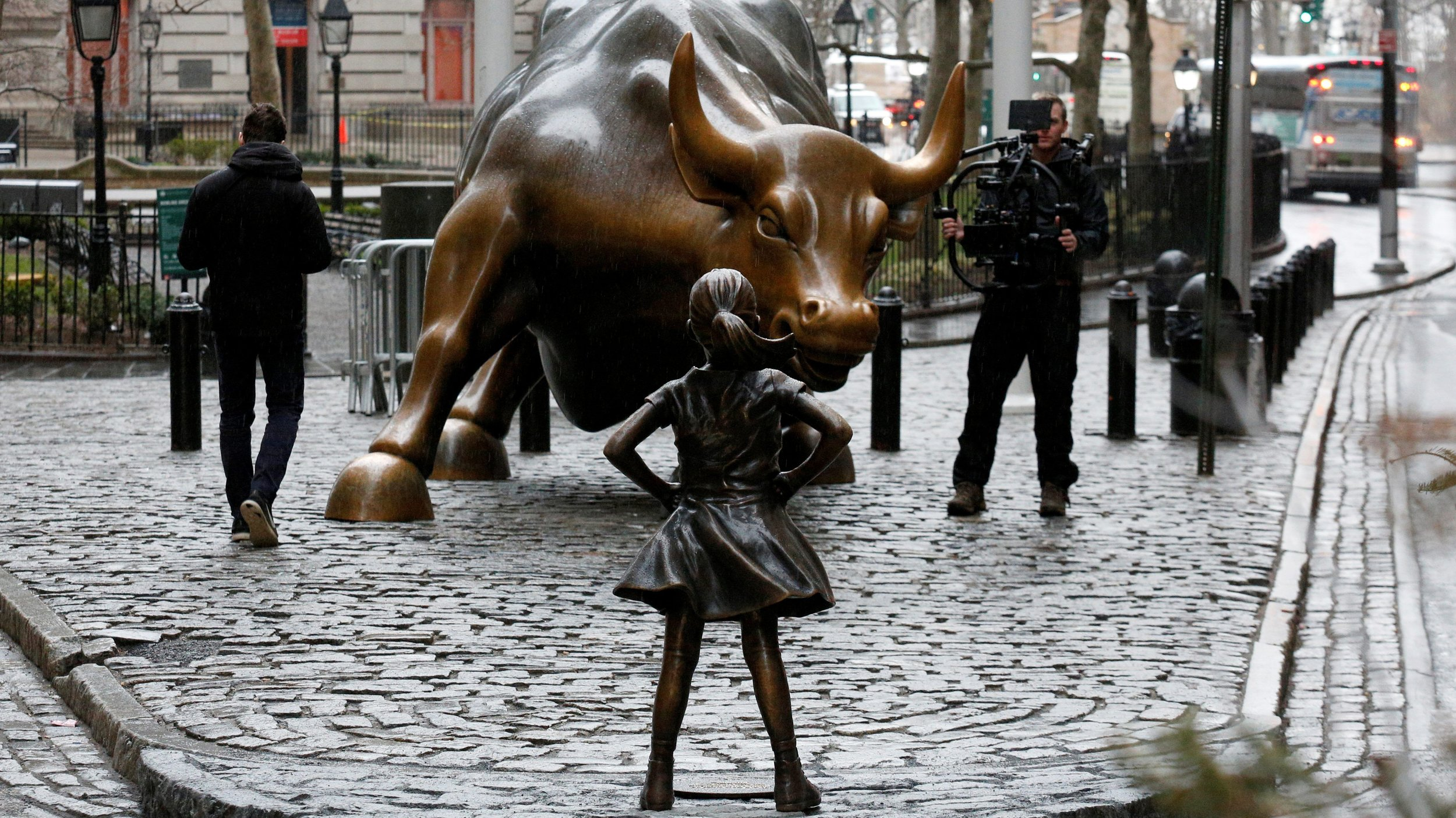 The veteran of Wall St, the Charging Bull being stared down by a newcomer - the Fearless Girl,  photo from Quartz