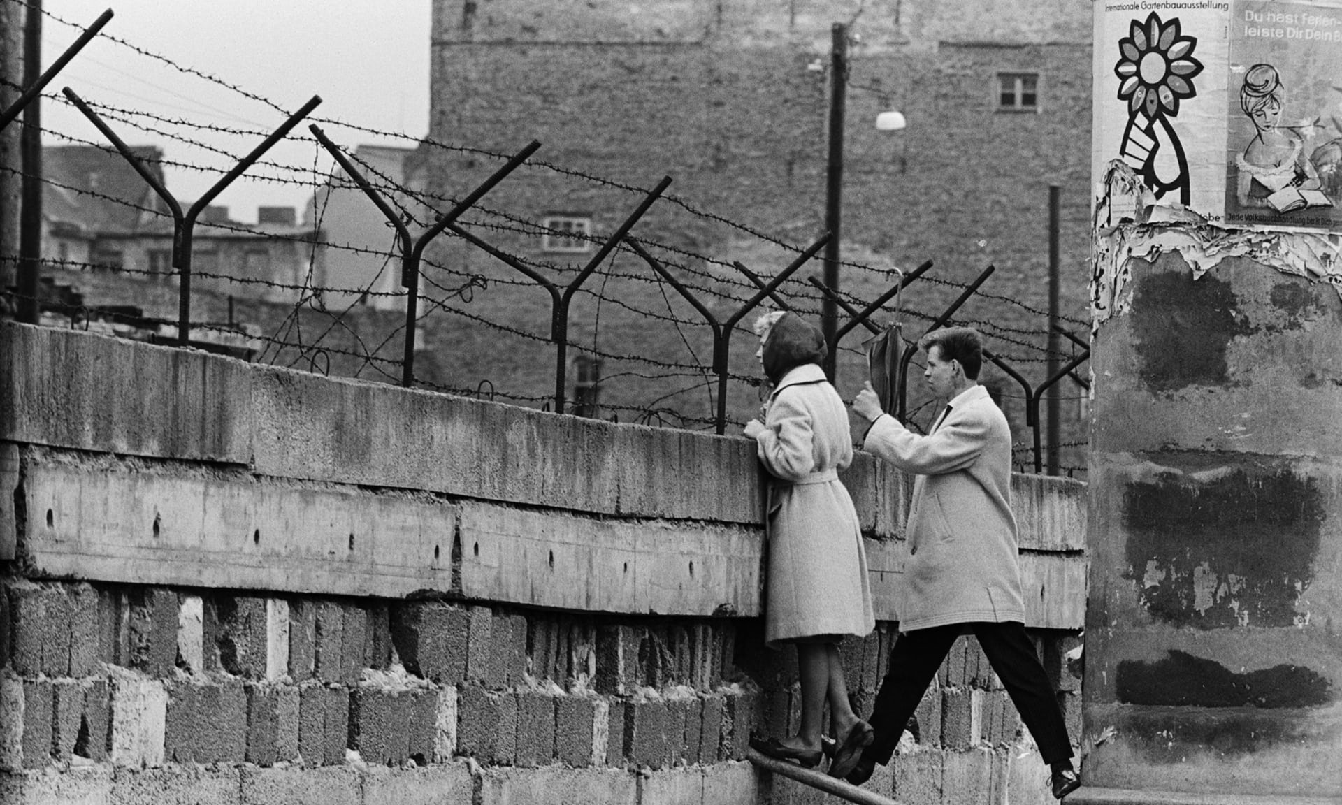 A young woman peeks over the newly erected Berlin Wall to exchange a few words with her mother,  photo from The Guardian