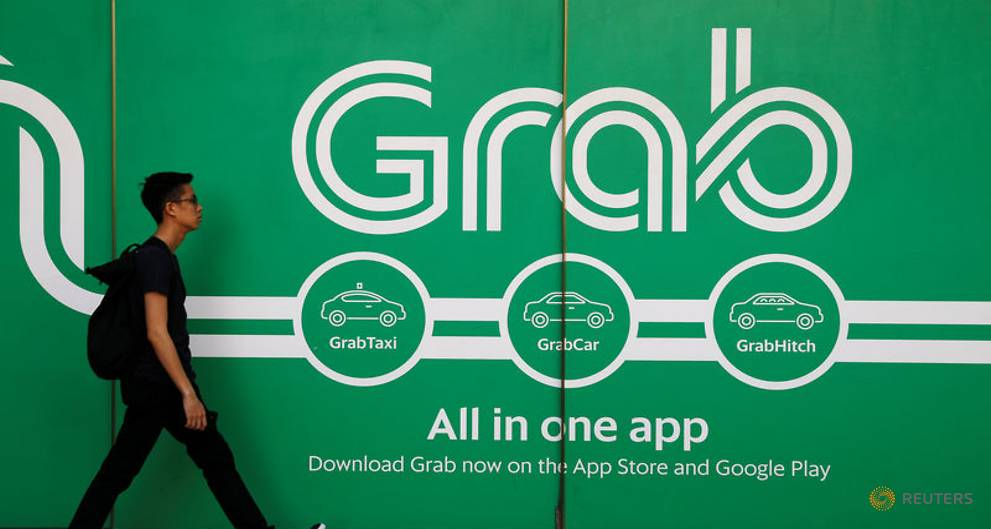 A man walks past the Grab logo,  photo from the Straits Times and Reuters